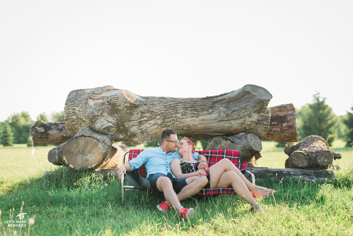Engaged couple relaxing on a bench in front of logs