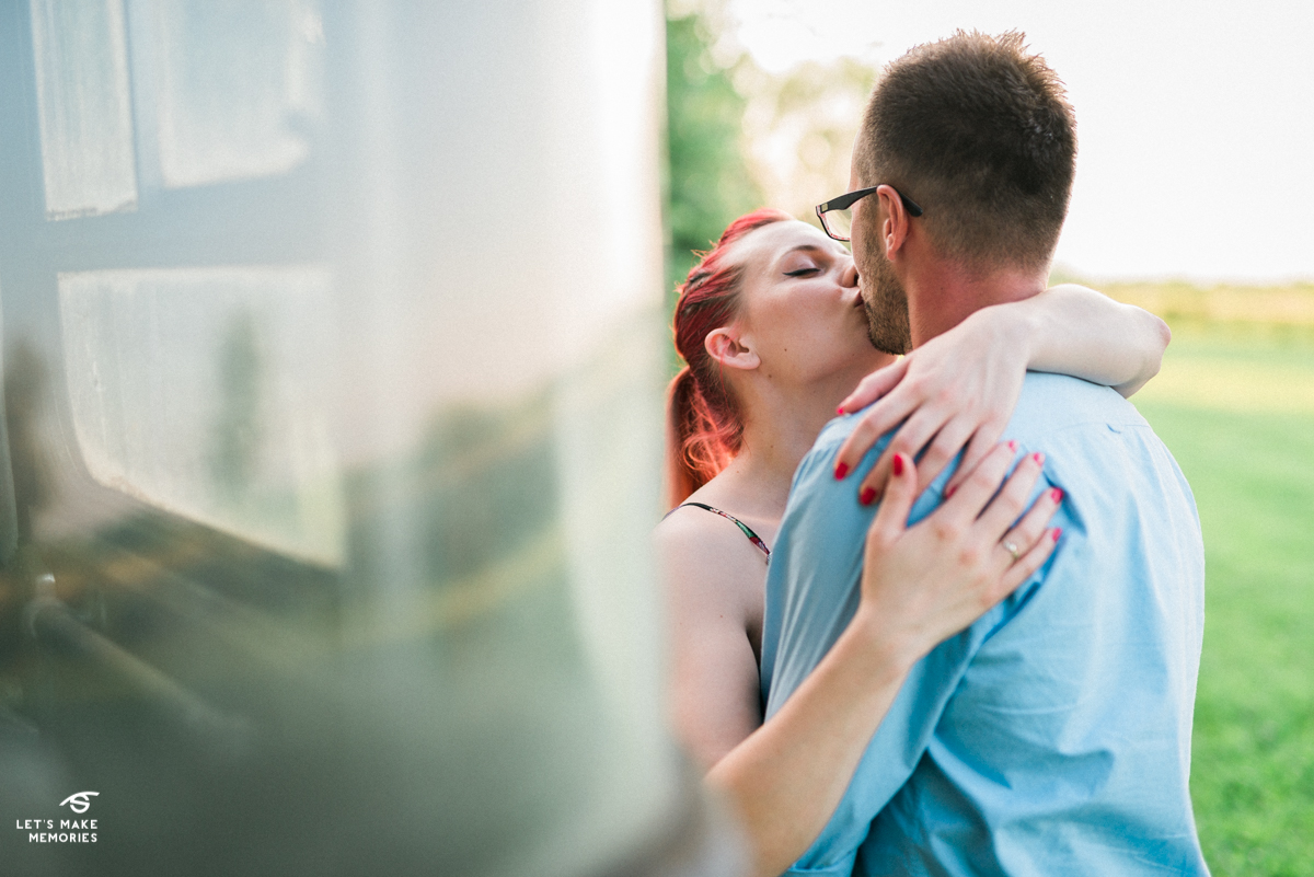 couple kissing in front of bee hive bus
