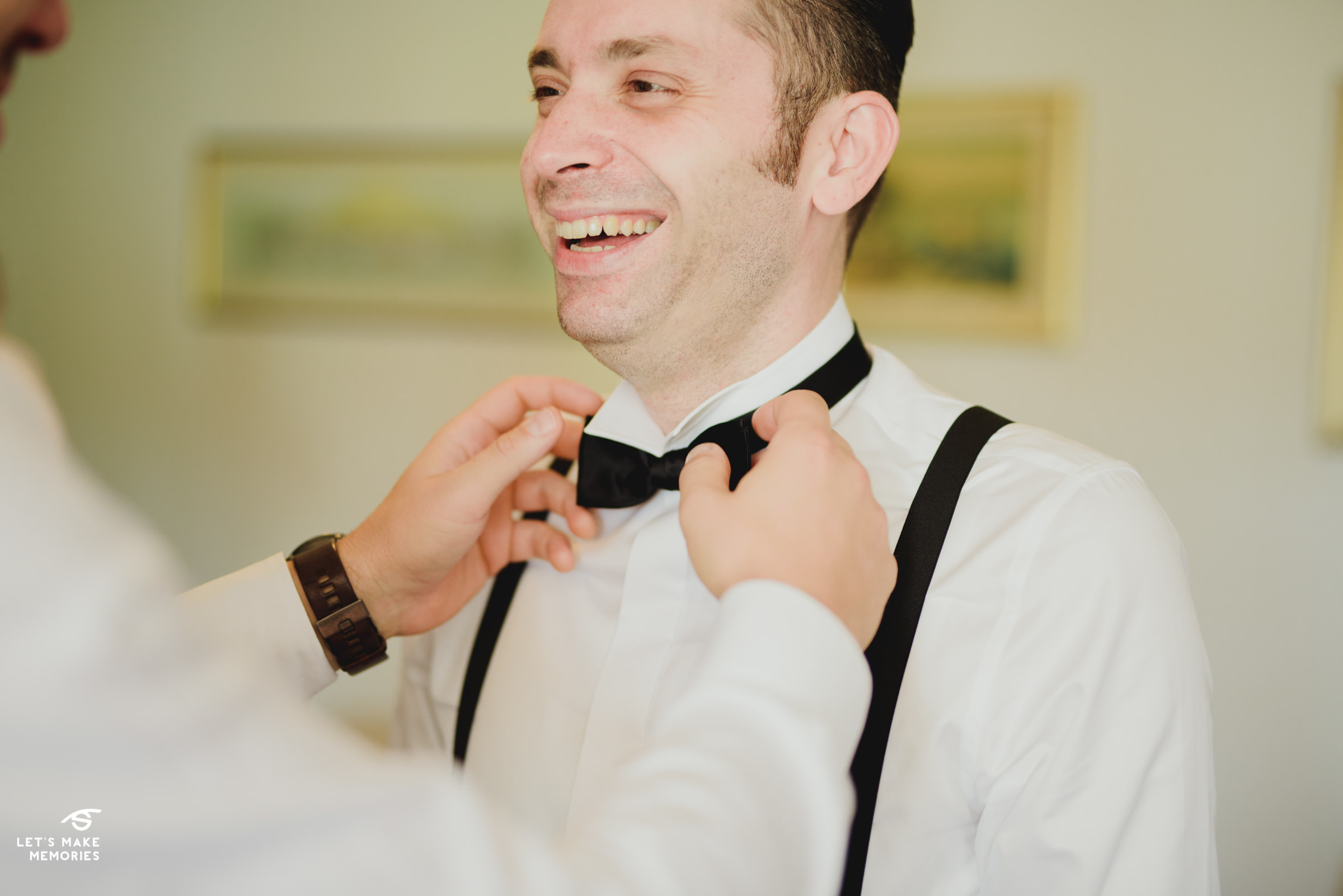 best man fixing grooms bow tie