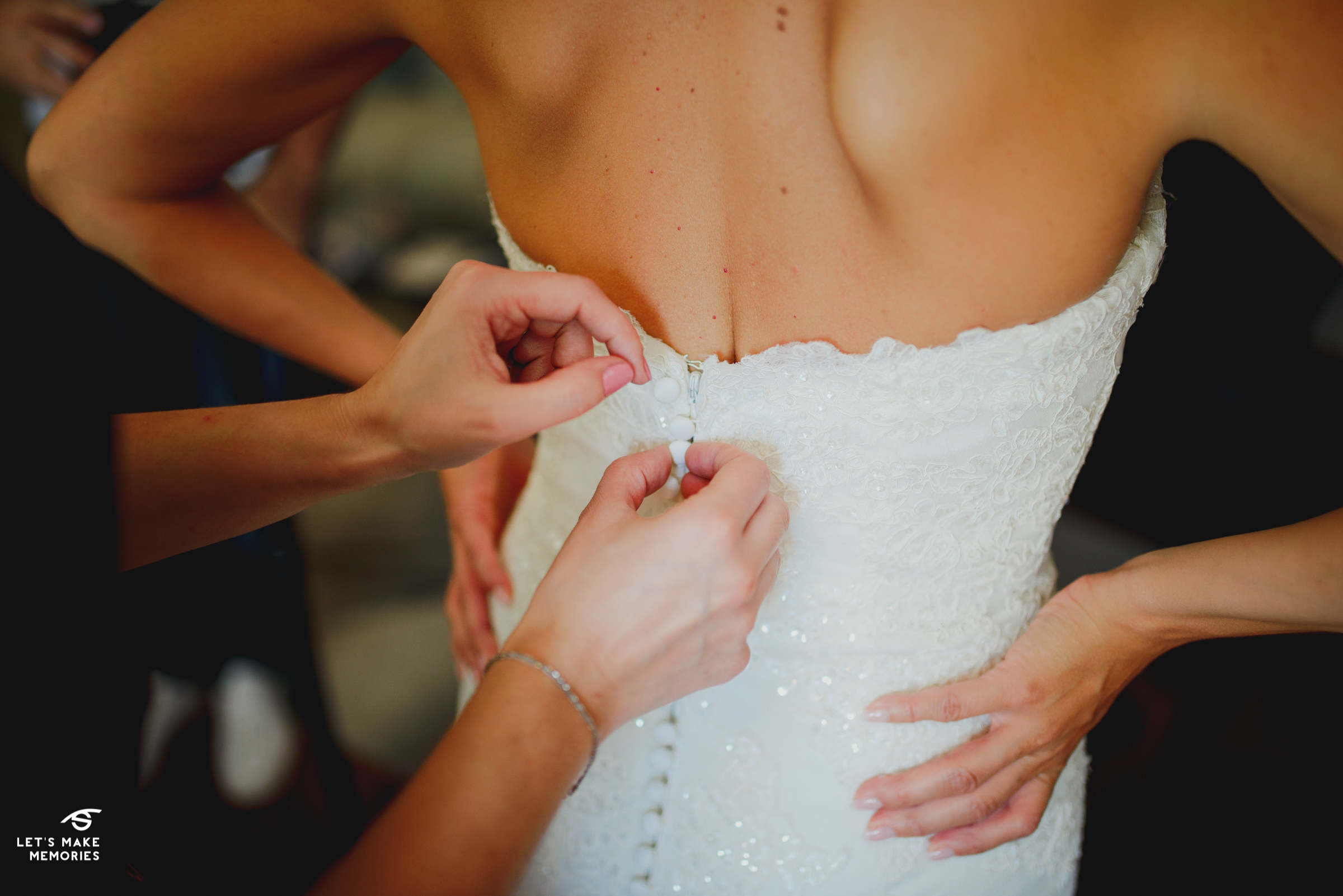 maid of honor buttoning up brides wedding dress