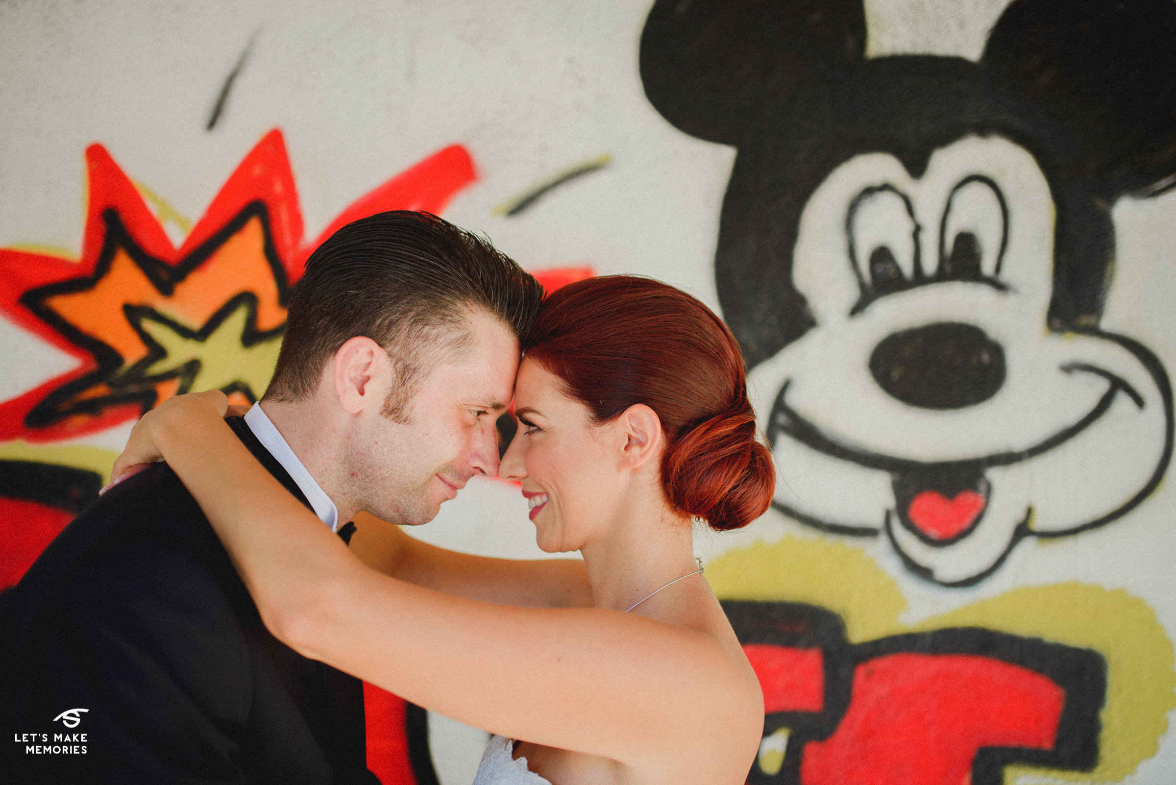 a couple hugging in front of MIckey Mouse graffitte