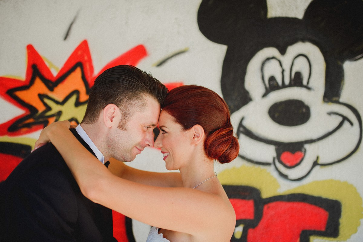 Couple hugging in front of graffite of Mickey Mouse on the market in Sinj
