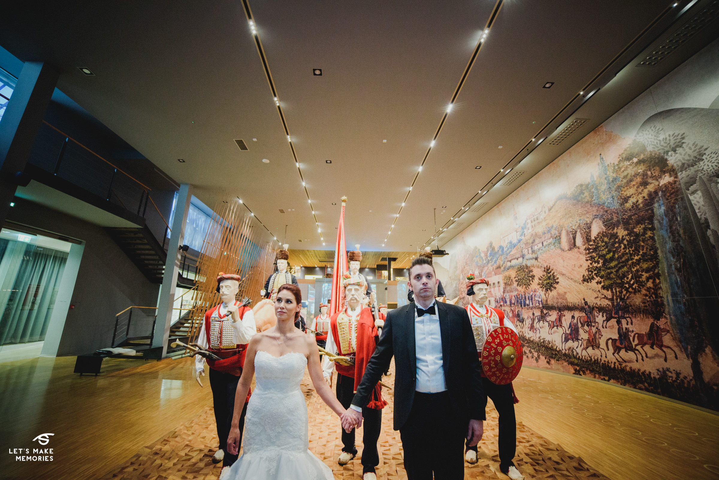 couple holding hands in front of the alka riders in the museum of alka in sinj