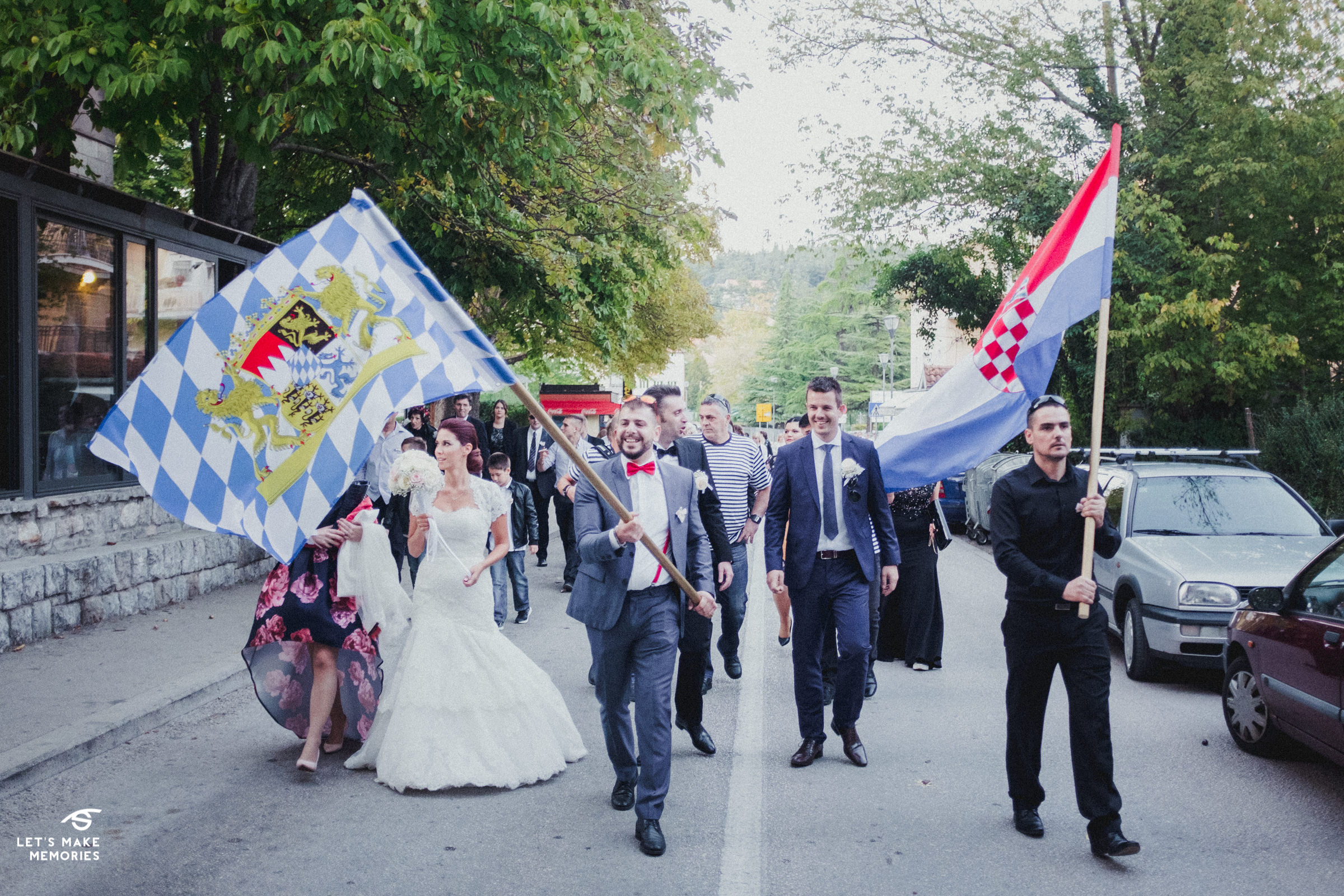 wedding party going towards the church with flags wawing