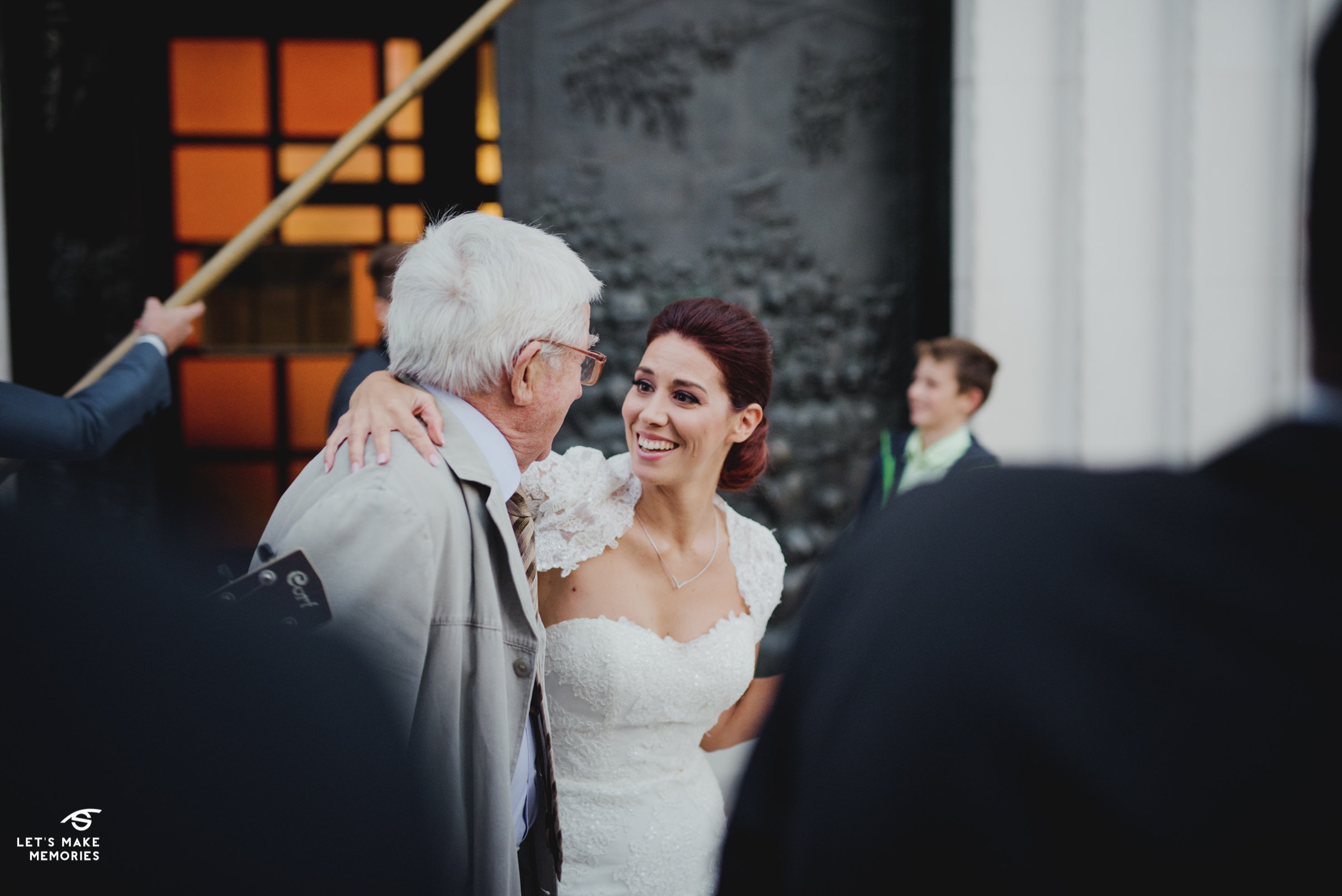 bride greeting the father of best man in front of the church