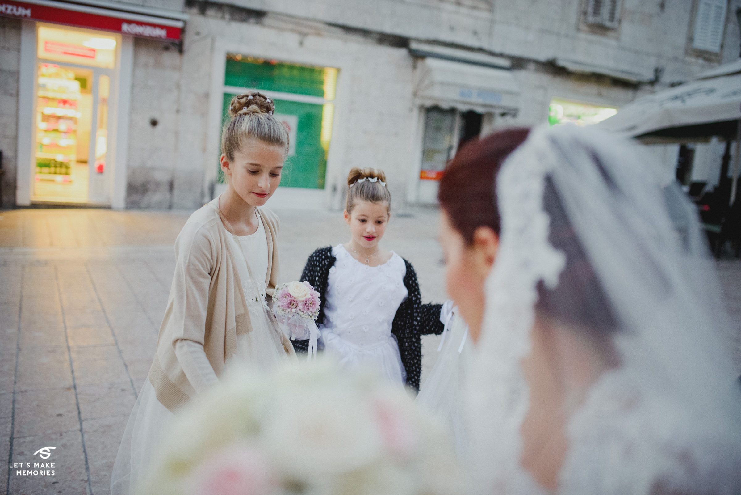 two little girls admiring the bride and her veil