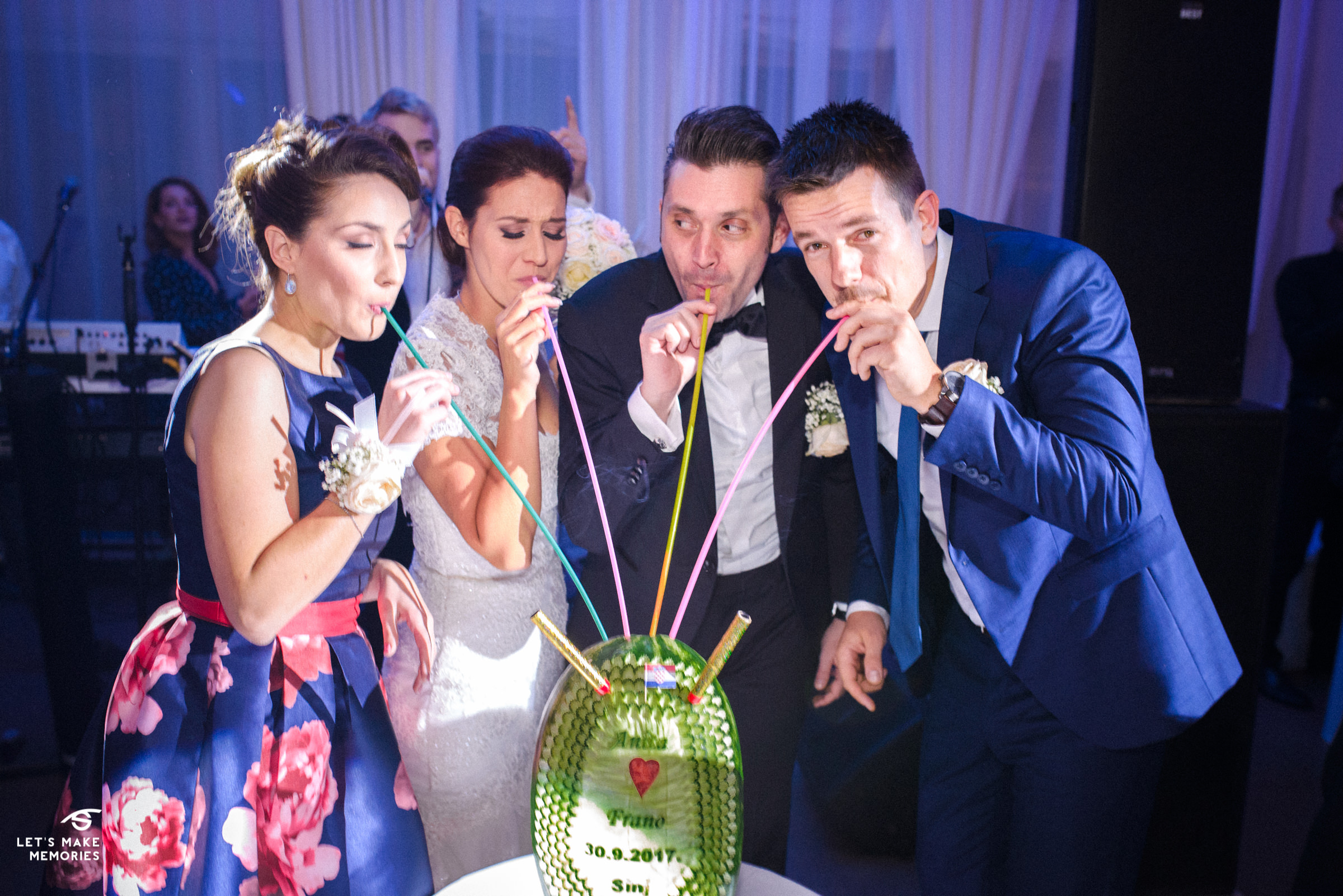 bride, groom, best man and maid of honor drinking a liquor out of the fruit