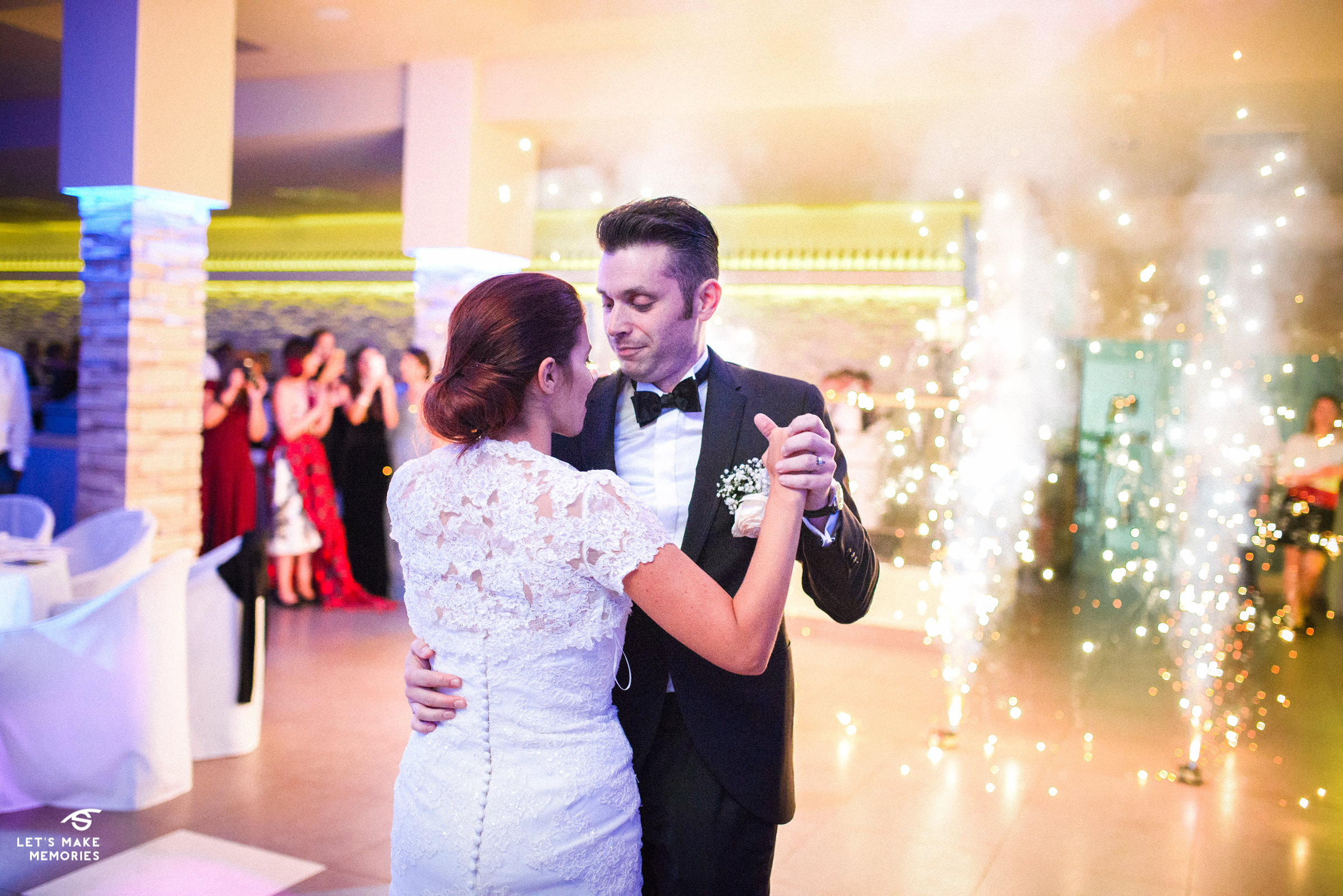 bride and groom dancing their first wedding dance in frond of sparkles and fireworks