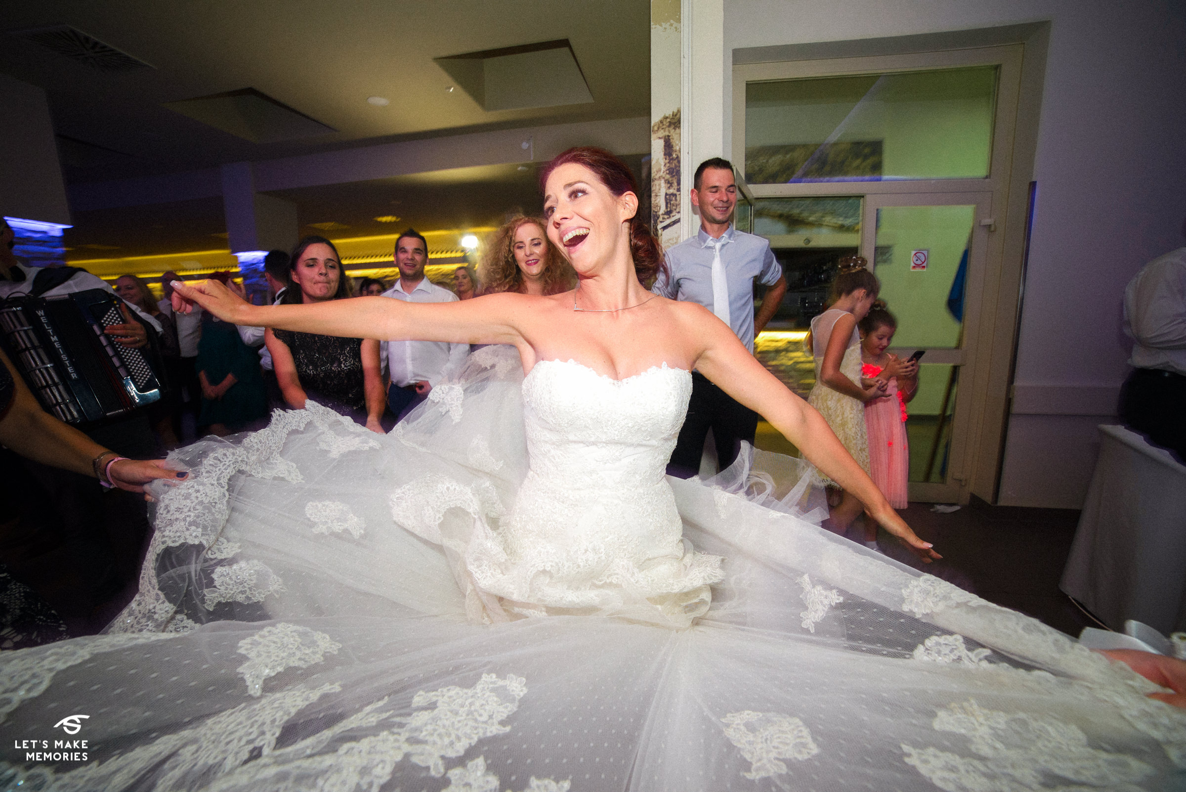bride dancing while her dress is being spread by the maids of honor