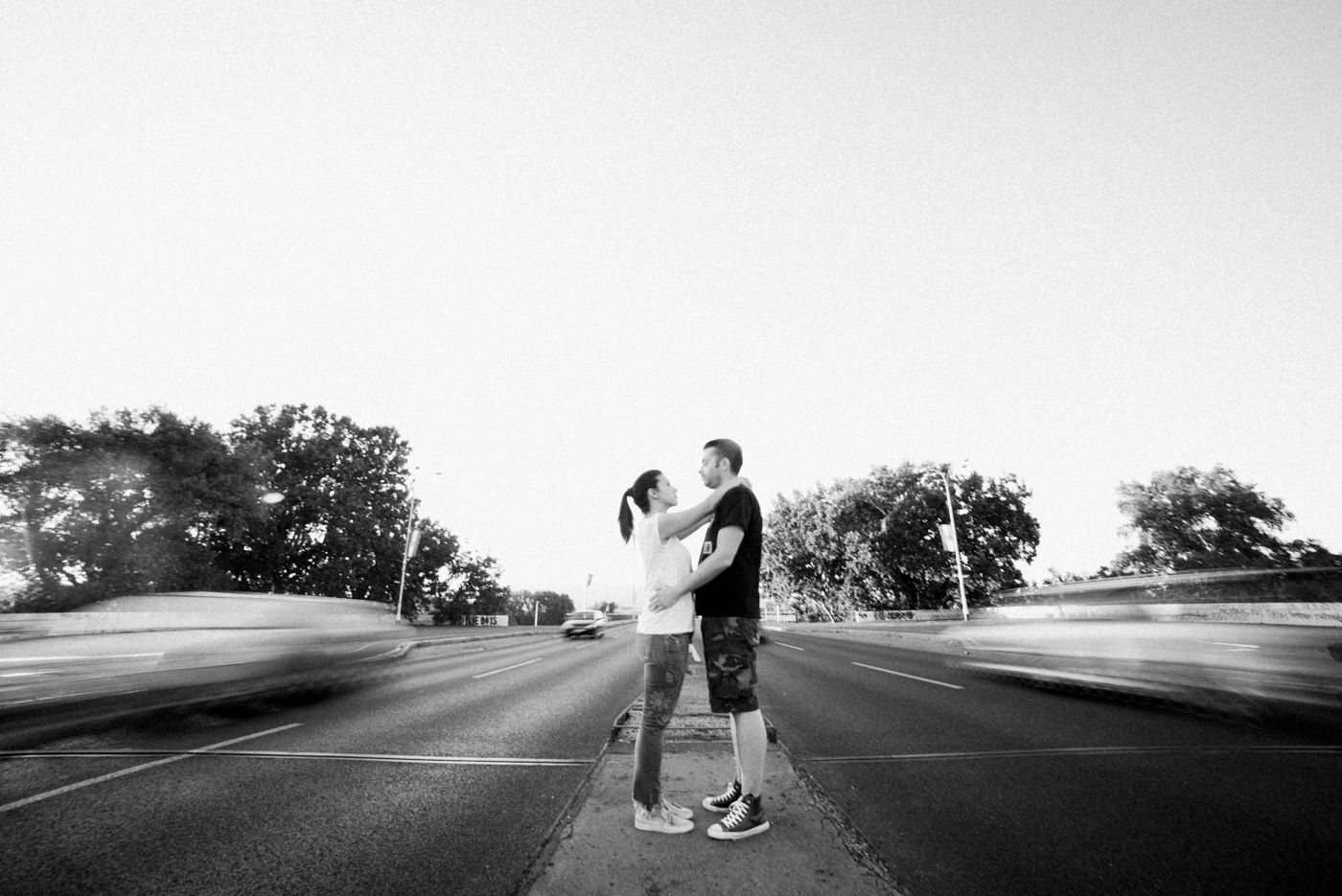 long eposure shot of couple hugging while cars are driving by