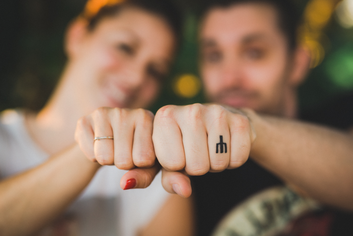 couple showing off their ring and tattoo