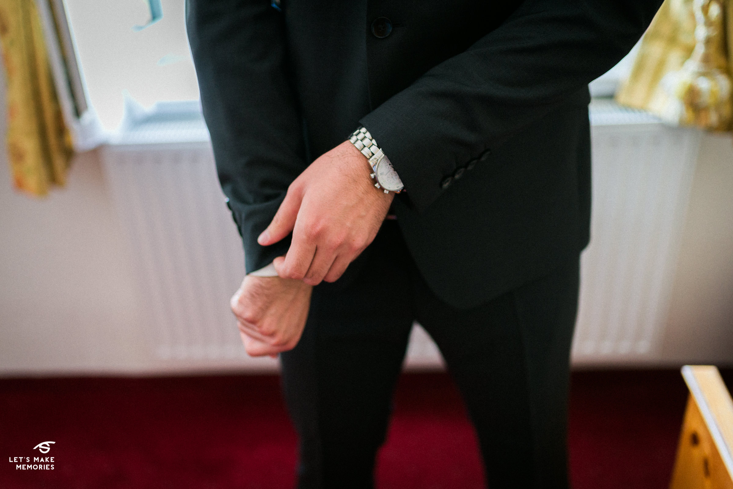 groom fixing his tuxedo to accomodate his watch