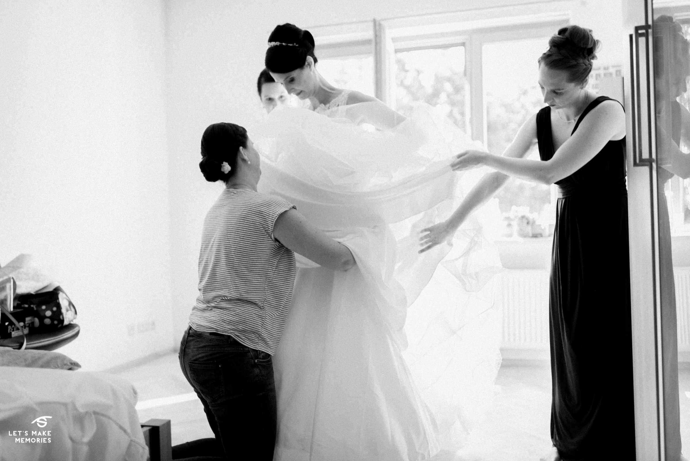brides sister helping her put on her dress