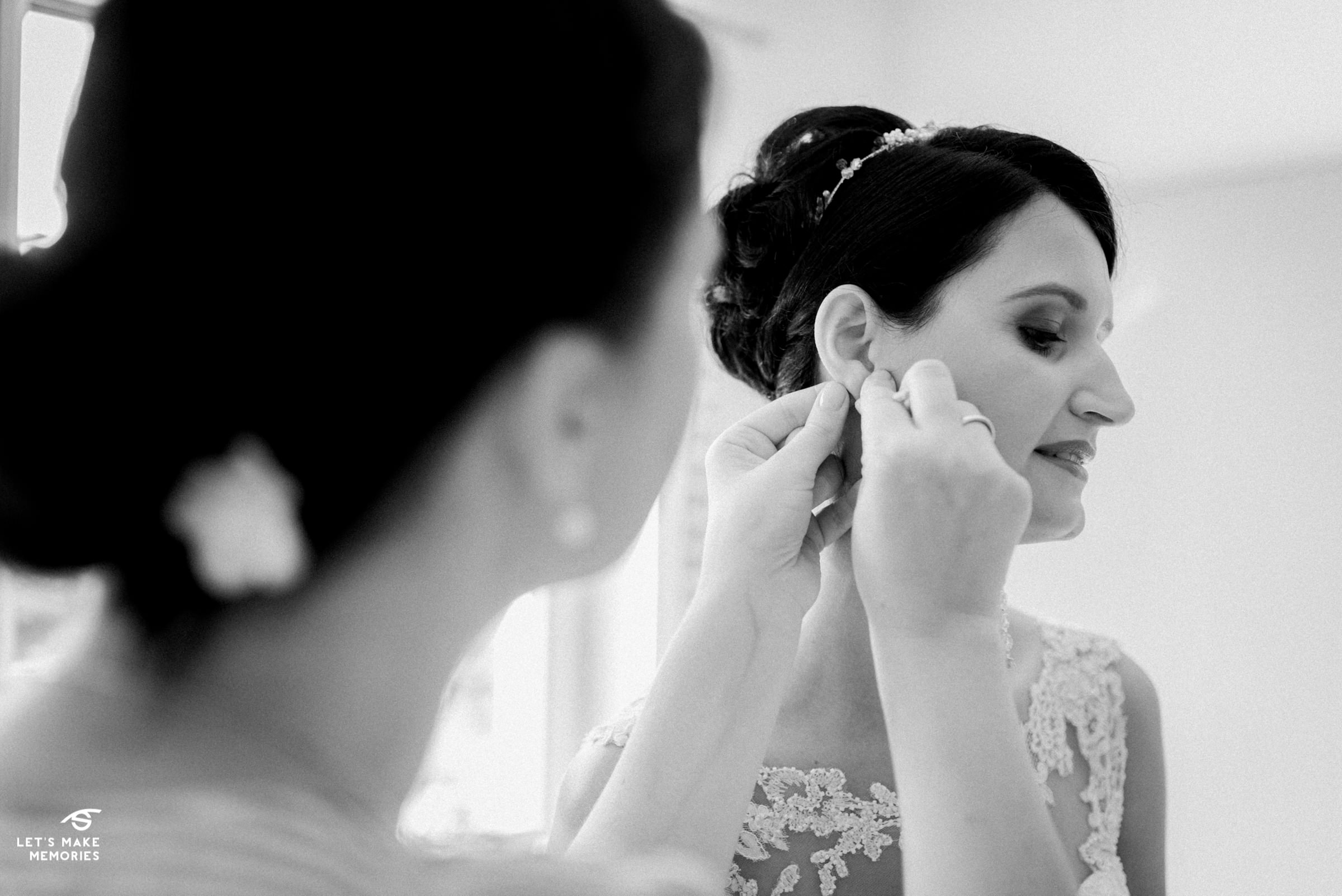 brides sister helping her put on earring