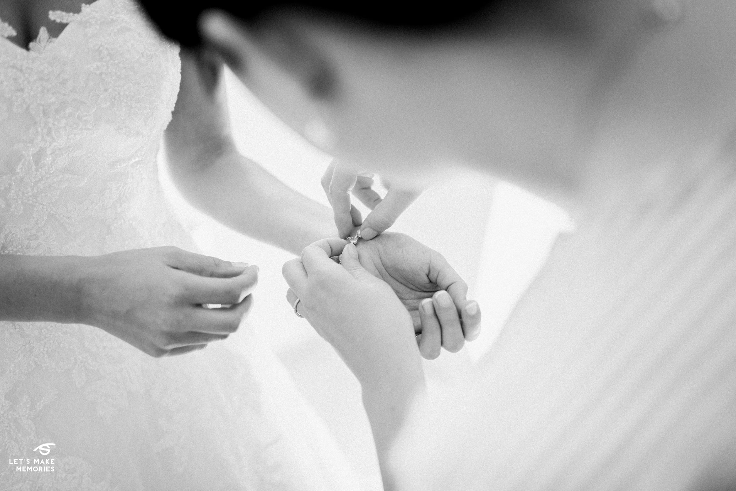 brides sister helping her put bracelet on