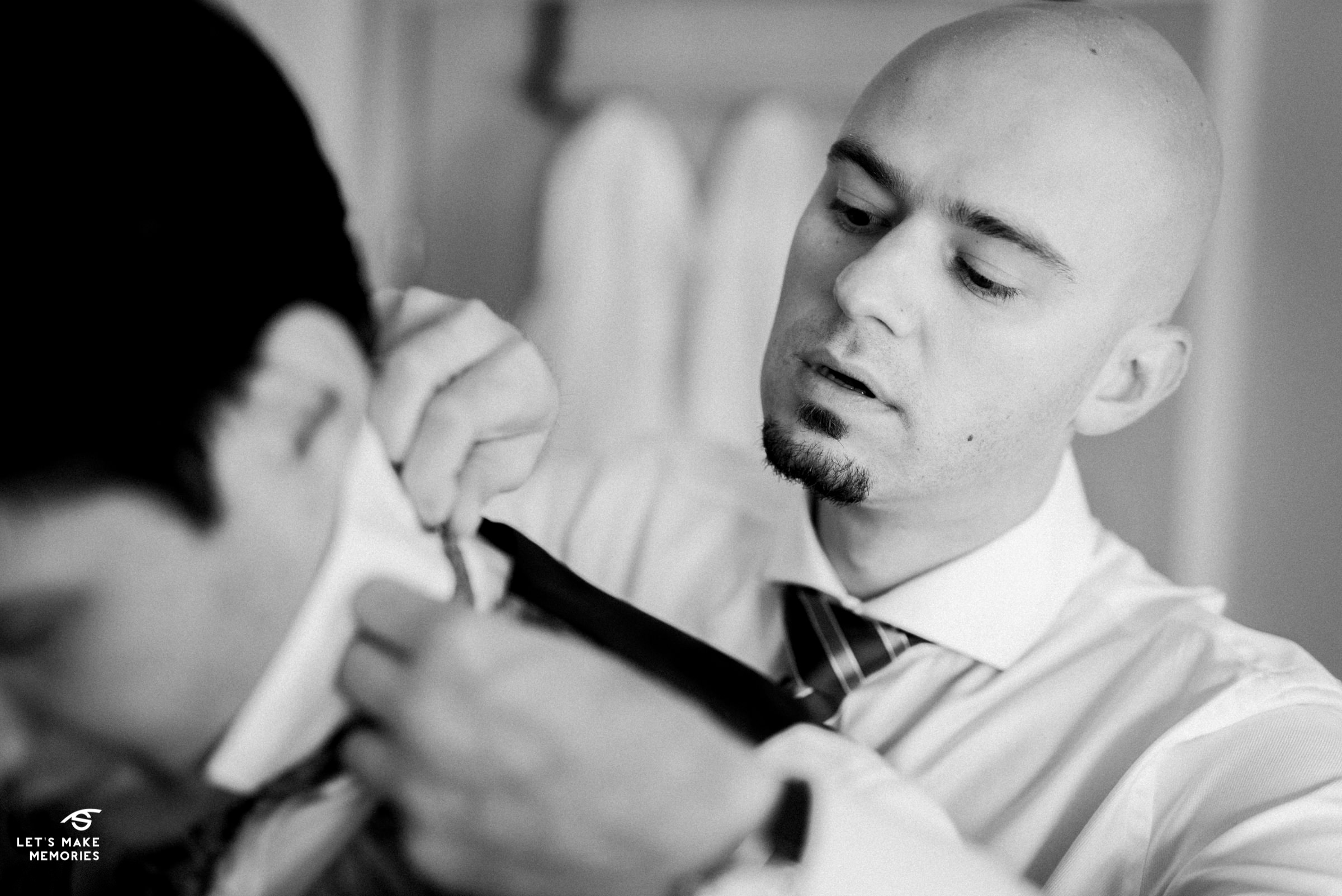 best man helping groom get his tie on