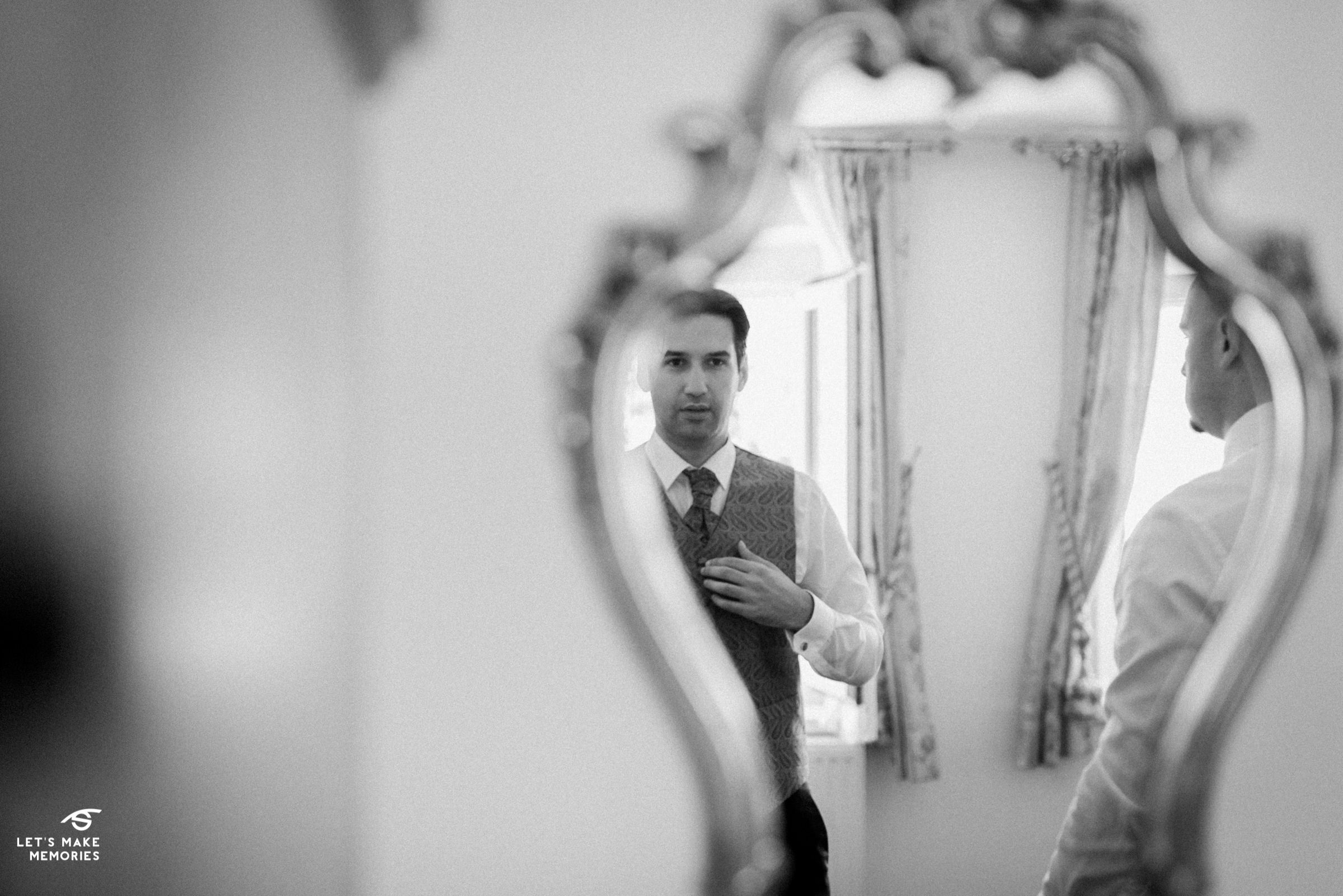 groom looking at himself in a mirror