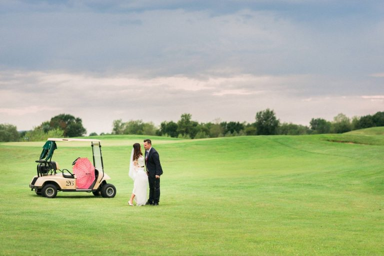 bride and groom on a golf course country club kissing