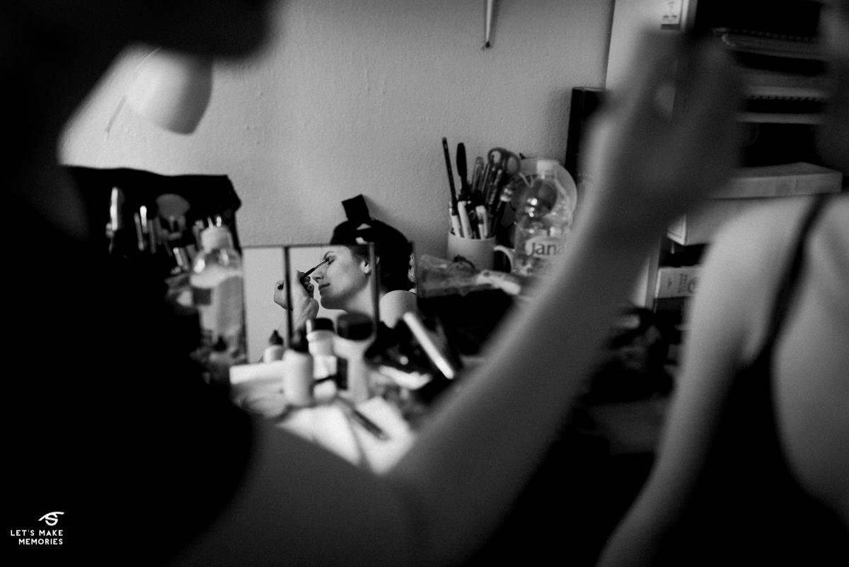 mirror shot of bride having her makeup done
