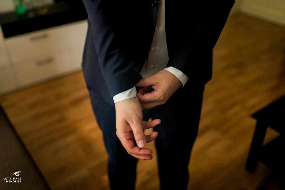 groom fixing his tuxedo