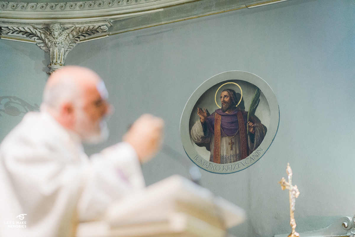 image of saint on the wall while priest is in foreground