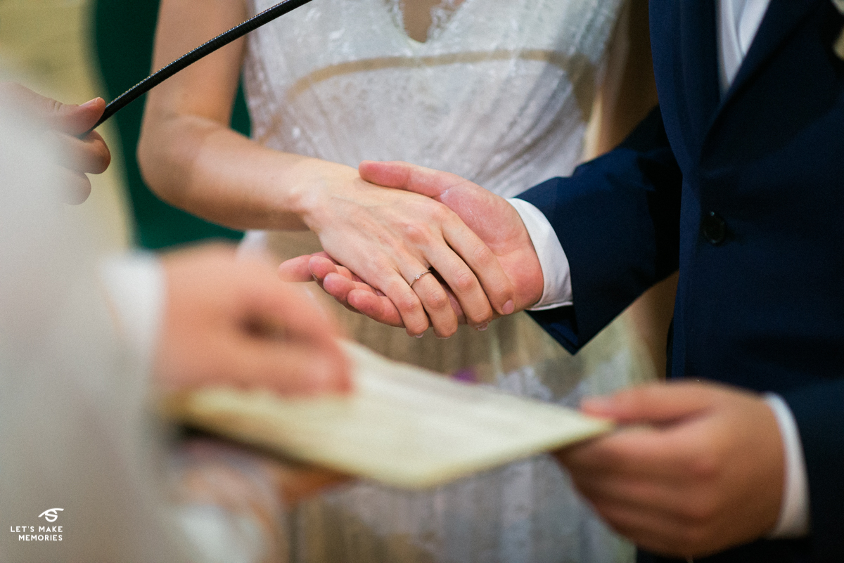 bride and groom holding hands while exchanging wows