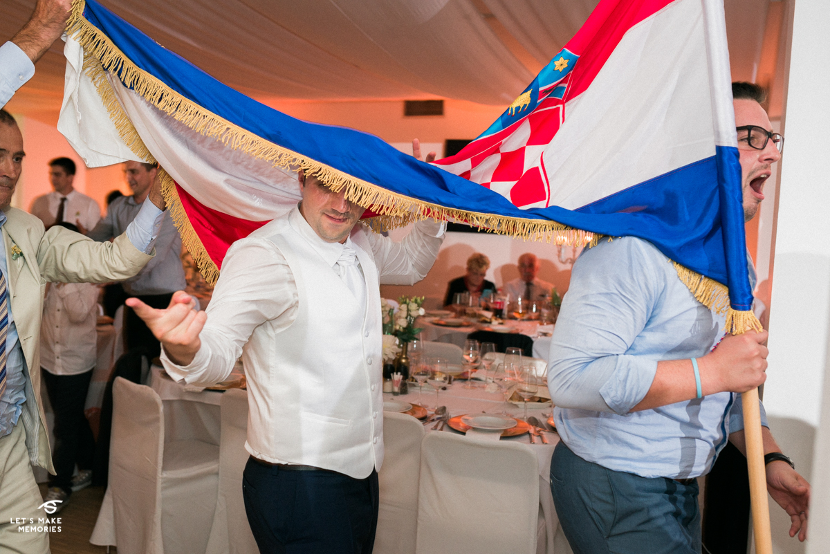 groom's head hidden under the flag while dancing to the music