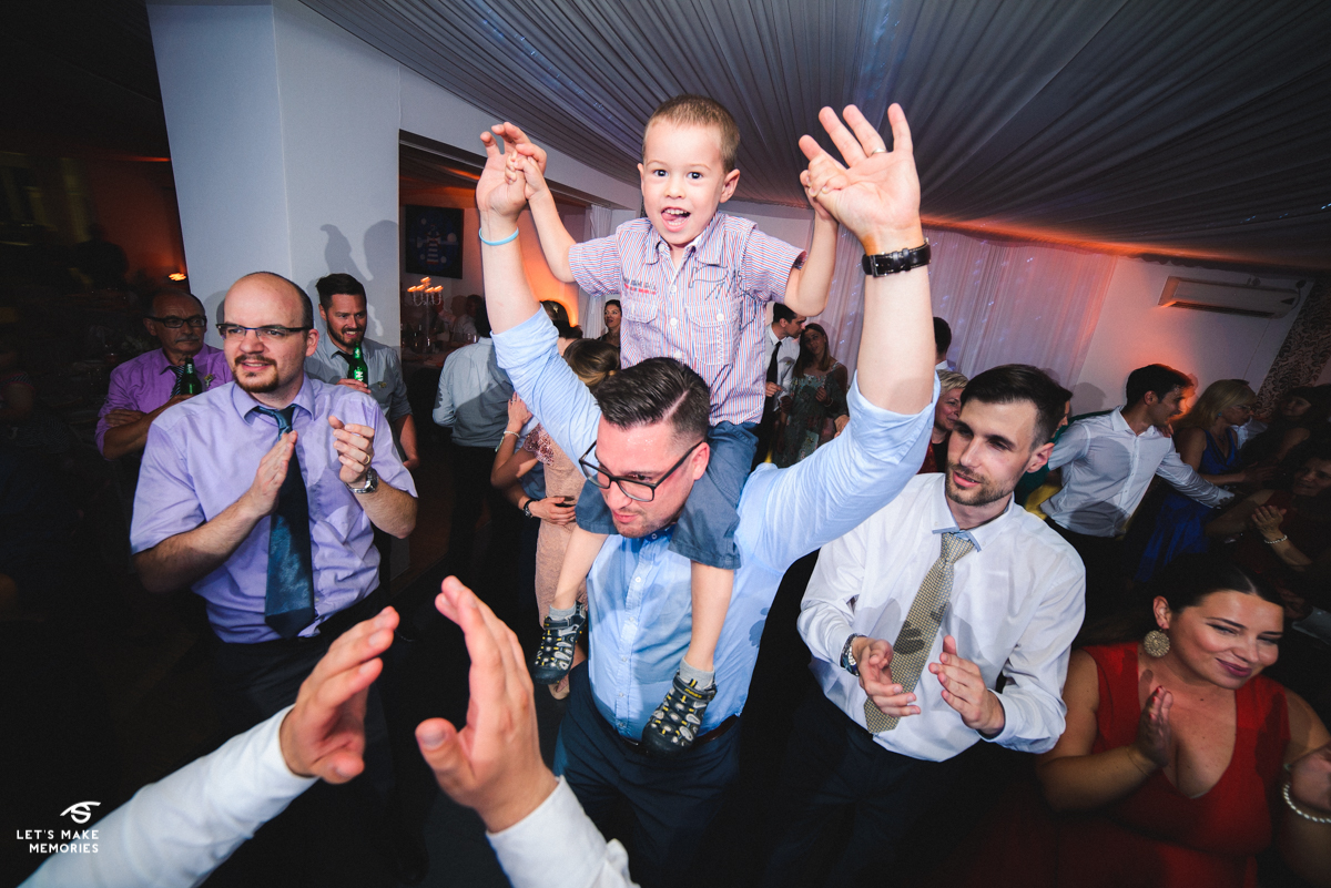 kid on his fathers shoulders dancing to the music