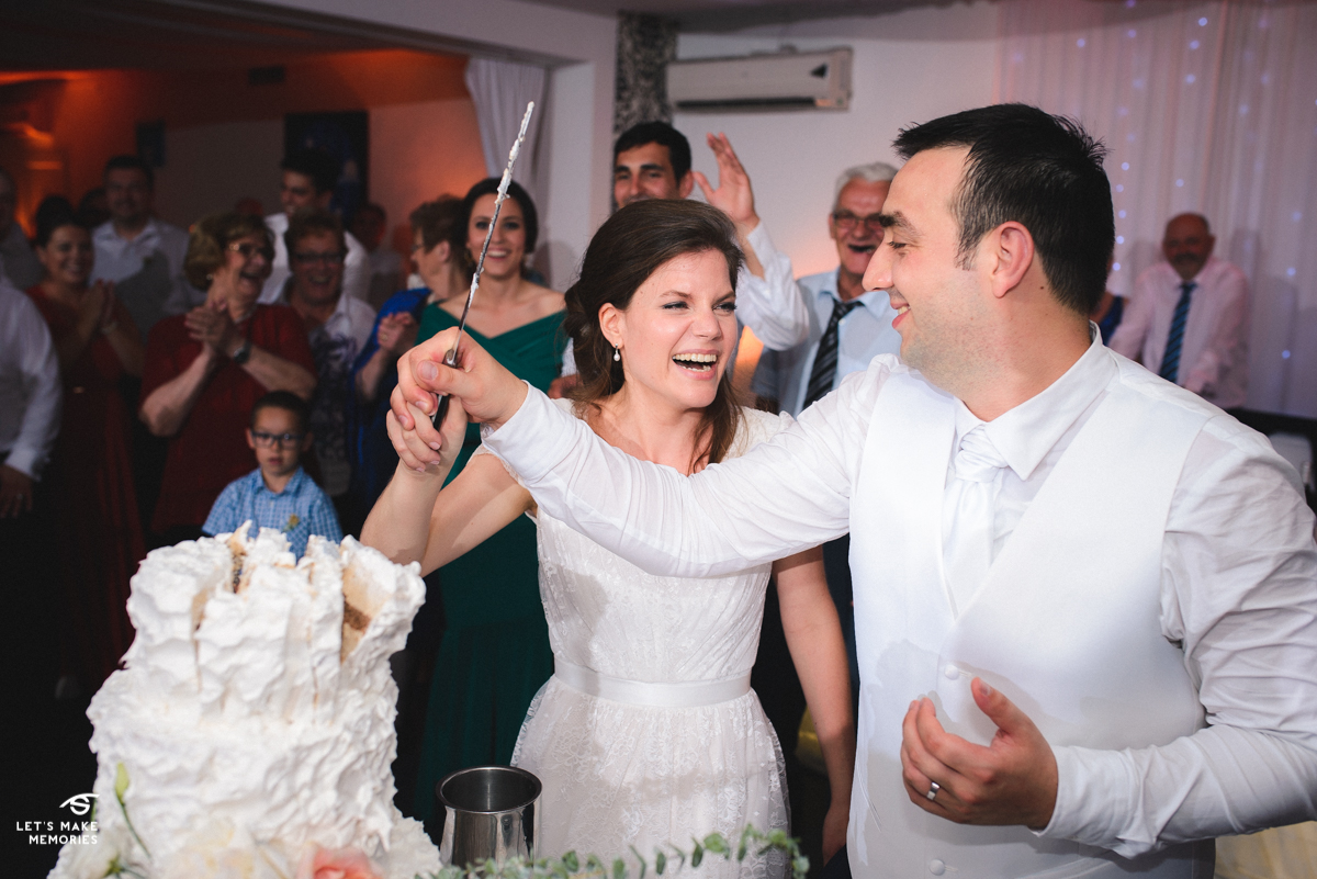 couple cutting the wedding cake, bride bursting into laughter