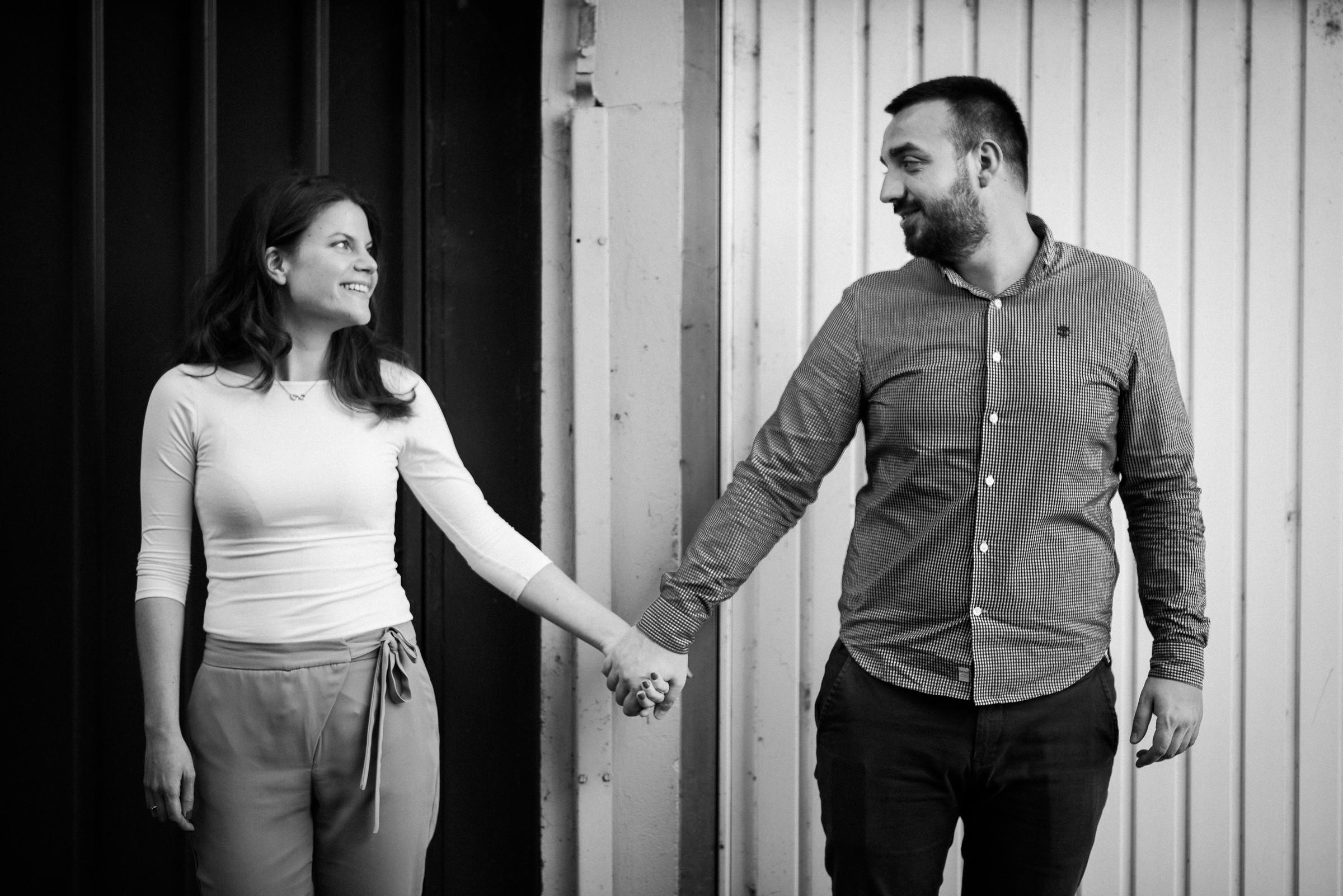 couple holding hands in front of garage door