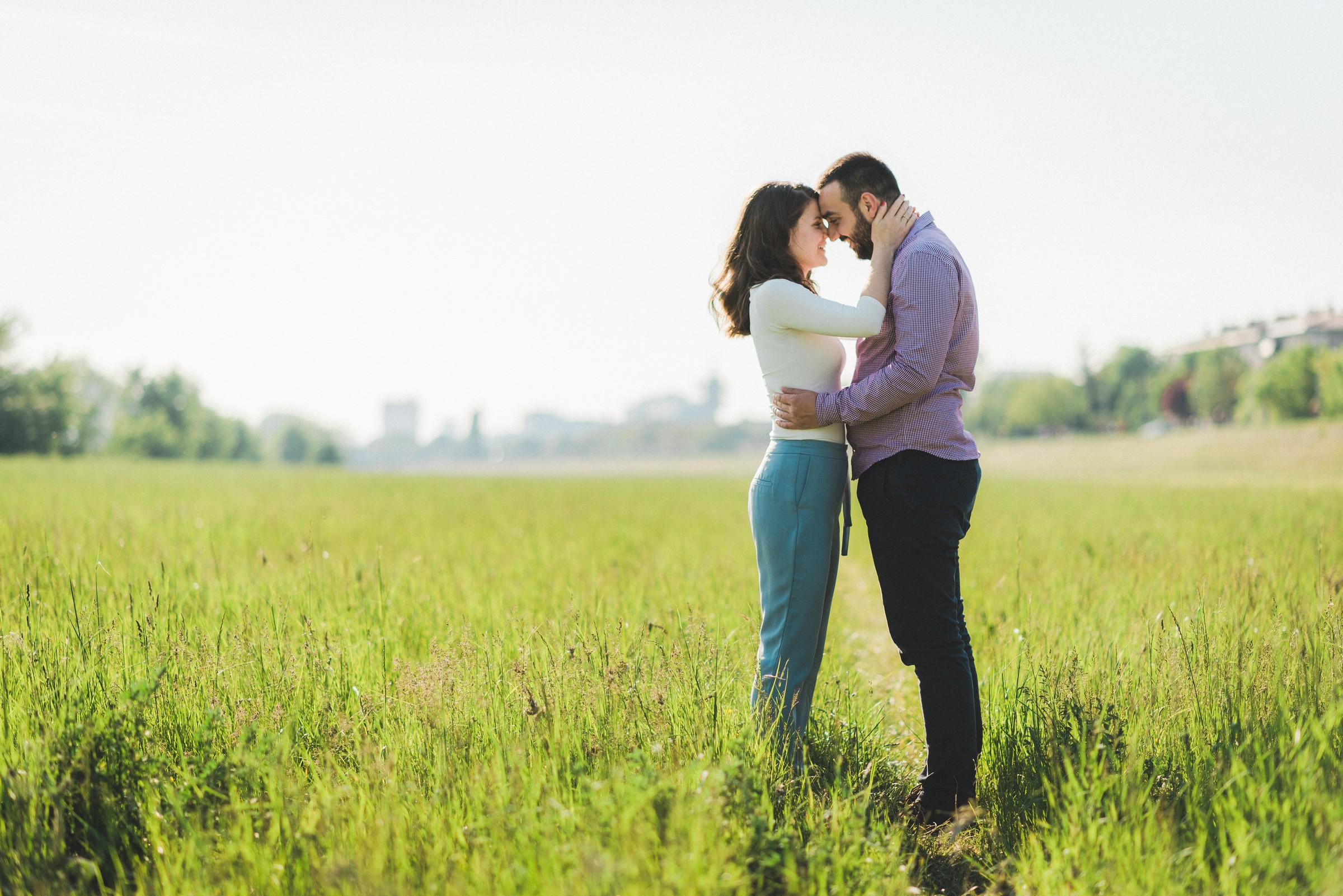 couple hugging in fields next to river Sava