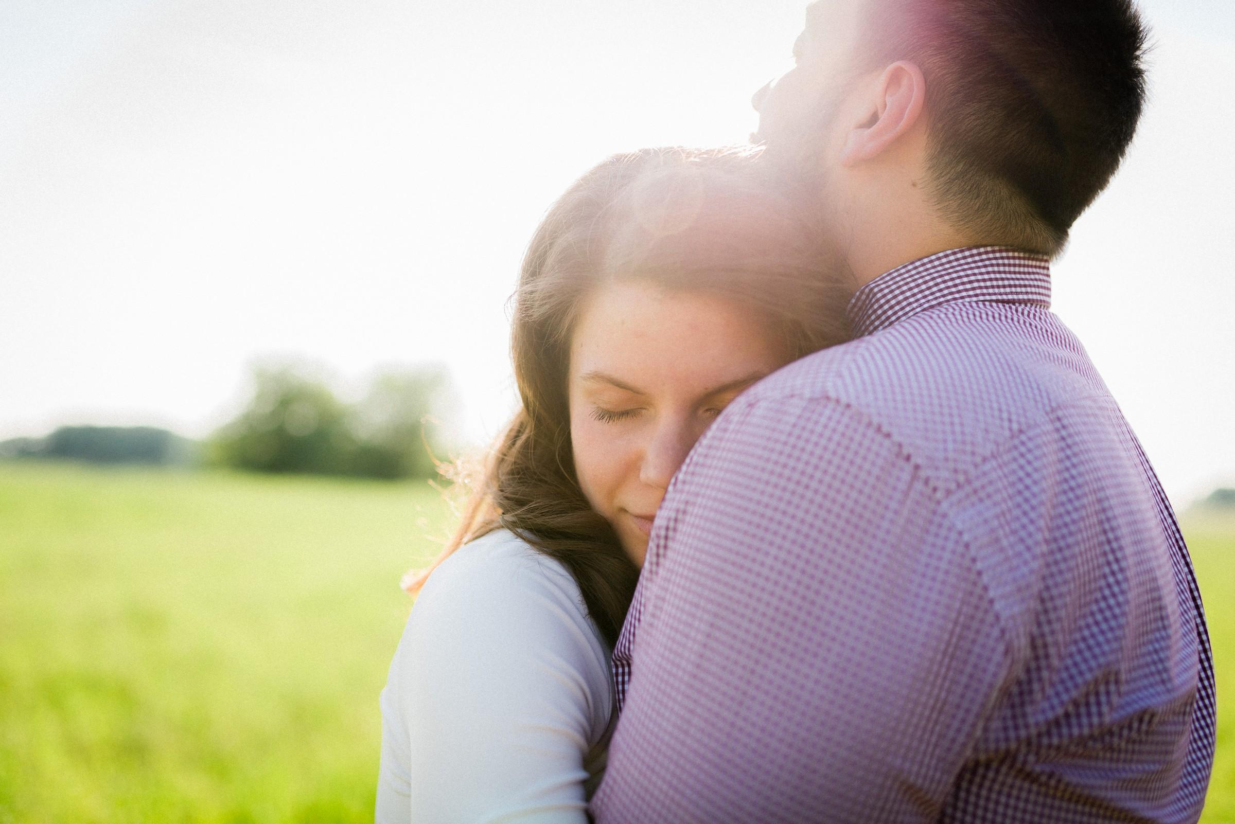 bride hugging groom with her eyes closed