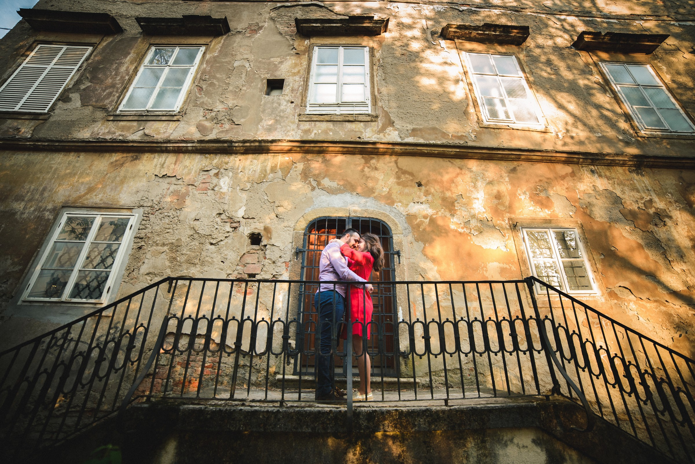 couple hugging in front of abandoned building on upper town in zagreb