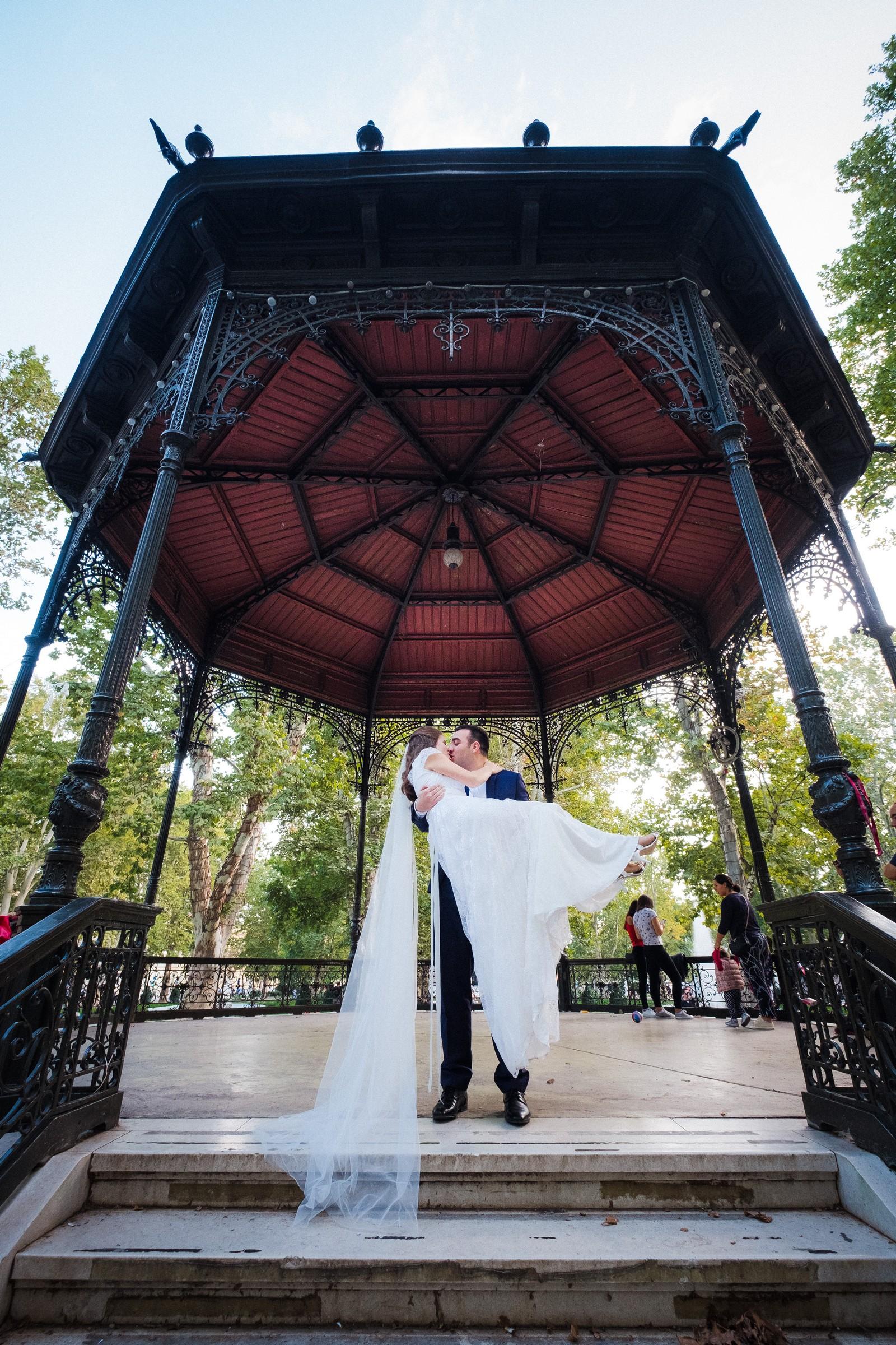 groom holding bride in his hands in Zrinjevac pavillion