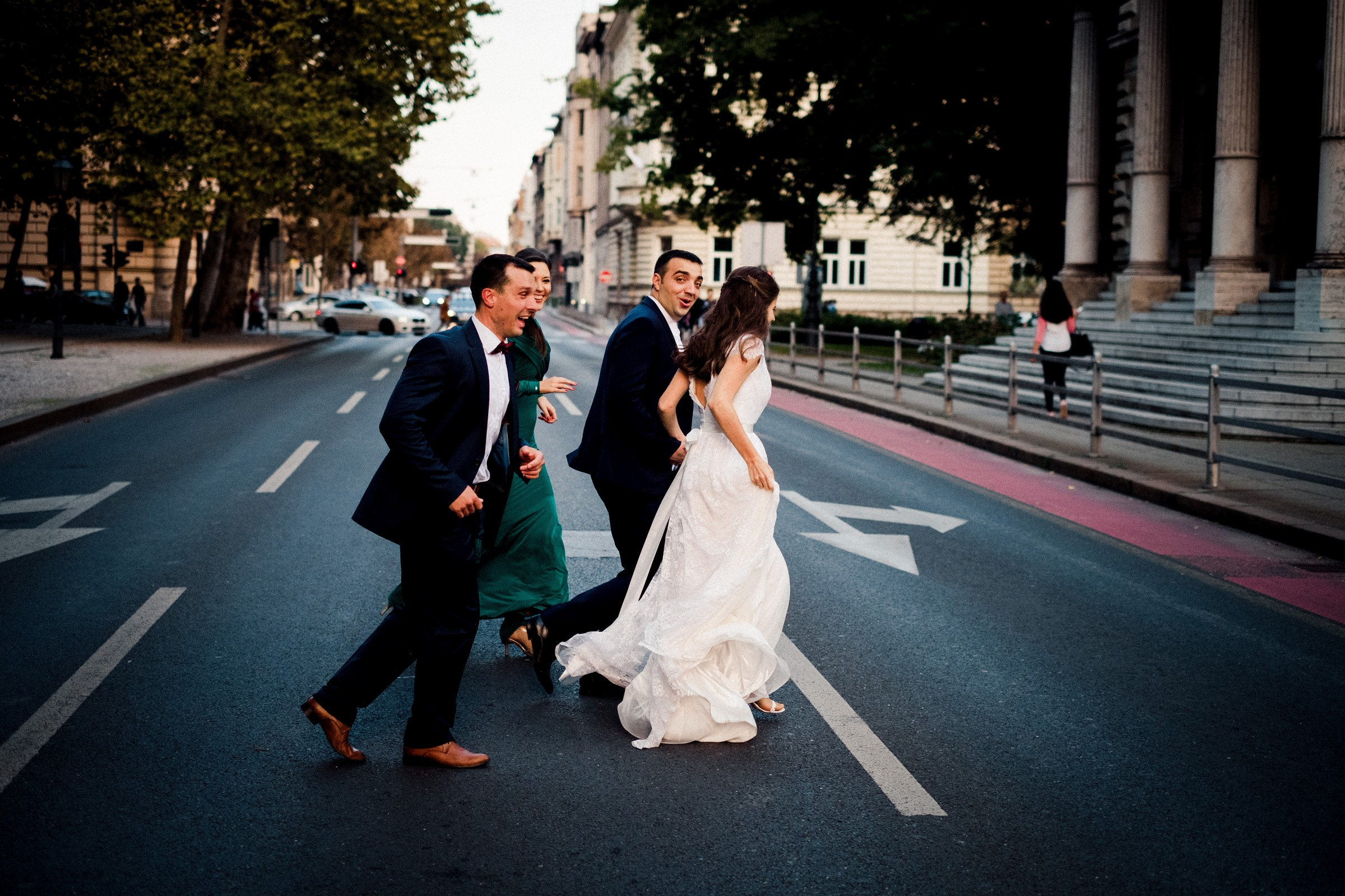 bridal party running across the street