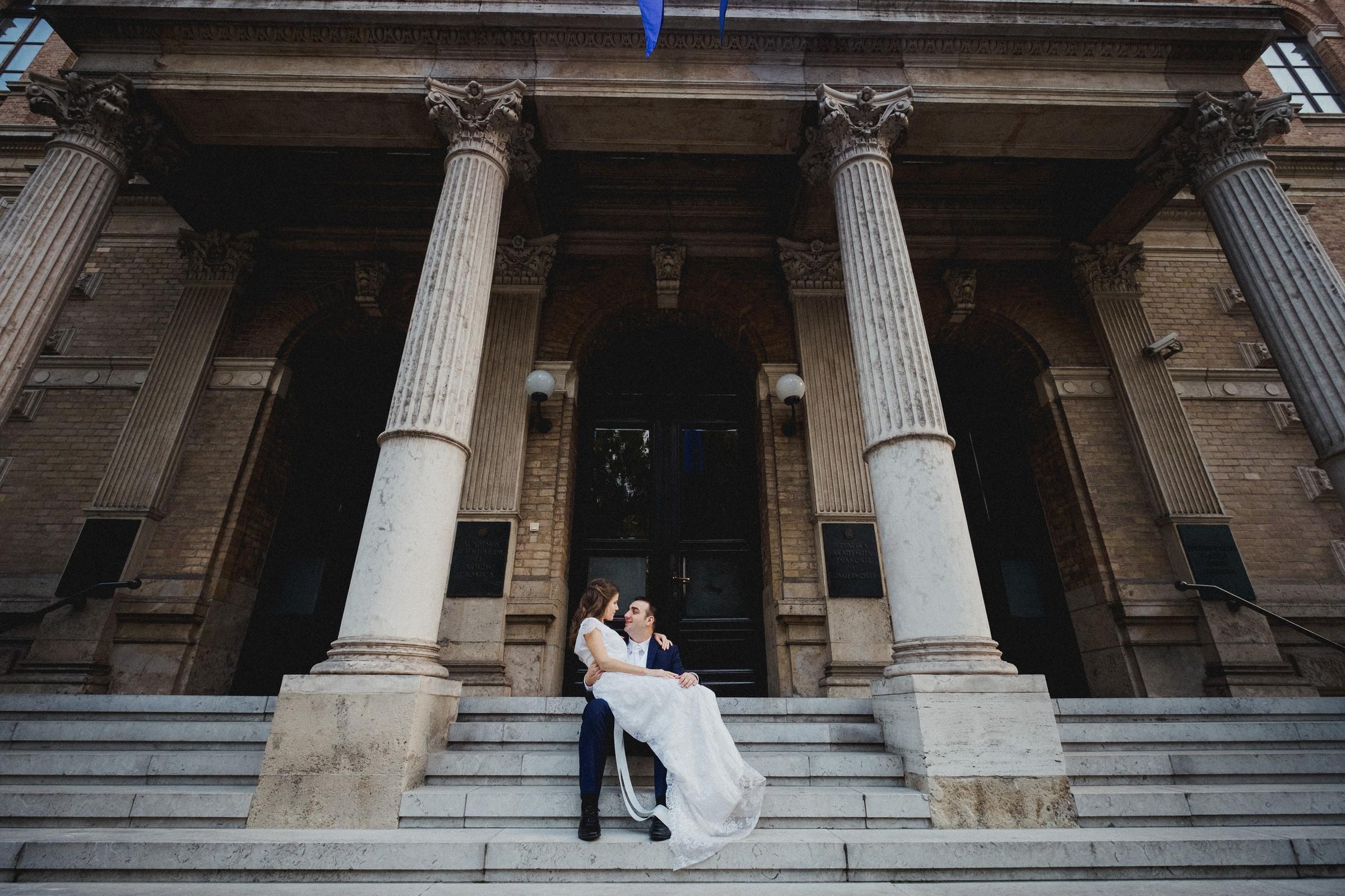 bride sitting in grooms lap on stairs across the street of zrinjevac park
