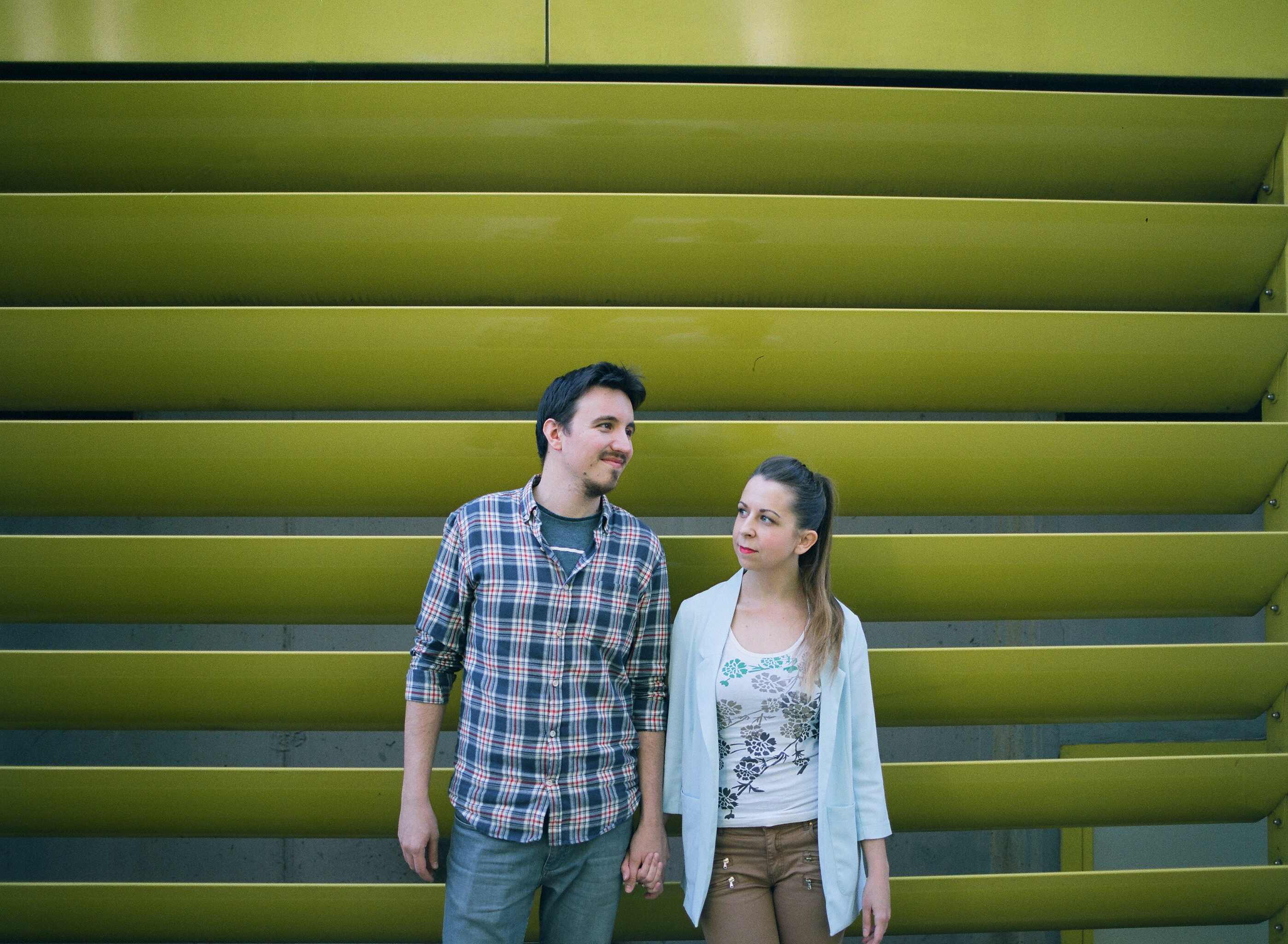 couple chilling in front of yellow fence. shot on medium format film, mamiya 645 pro tl, sekor 45mm f2.8