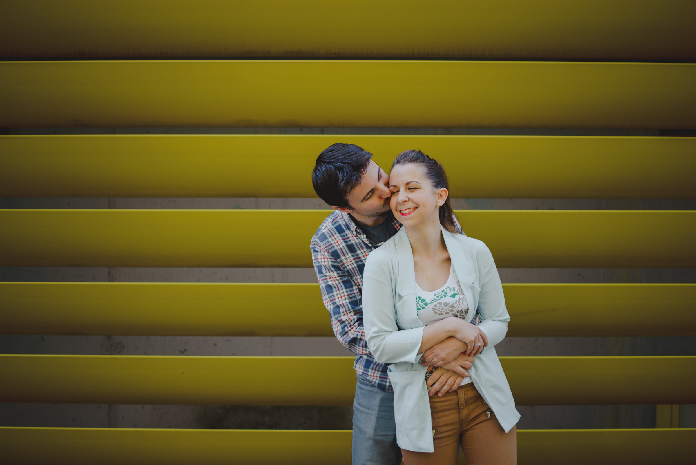 couple hugging and kissing in front of yellow fence, shot on medium format film, mamiya 645 pro tl and sekor 45 f2.8
