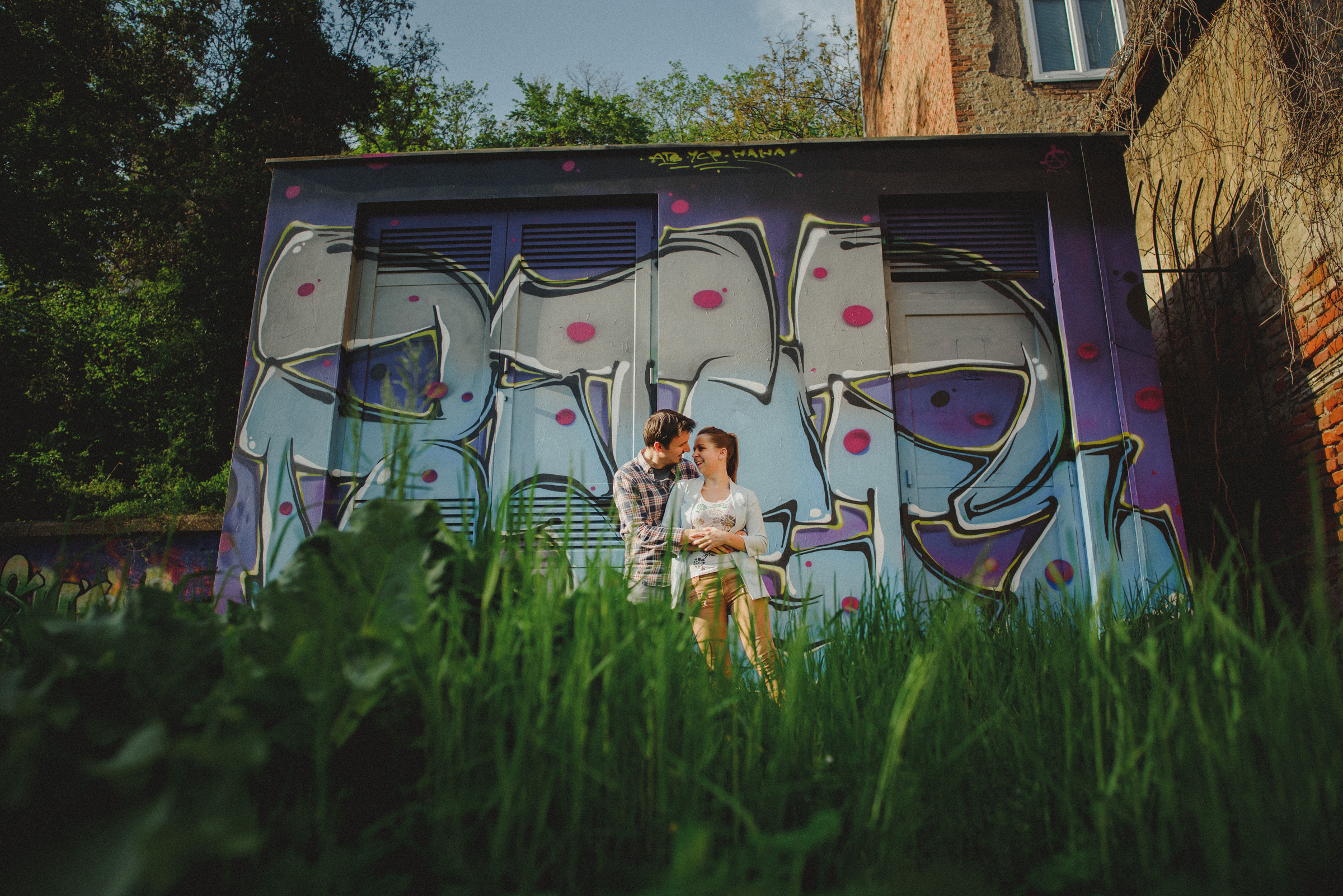 couple hugging in front of a graffiti wall