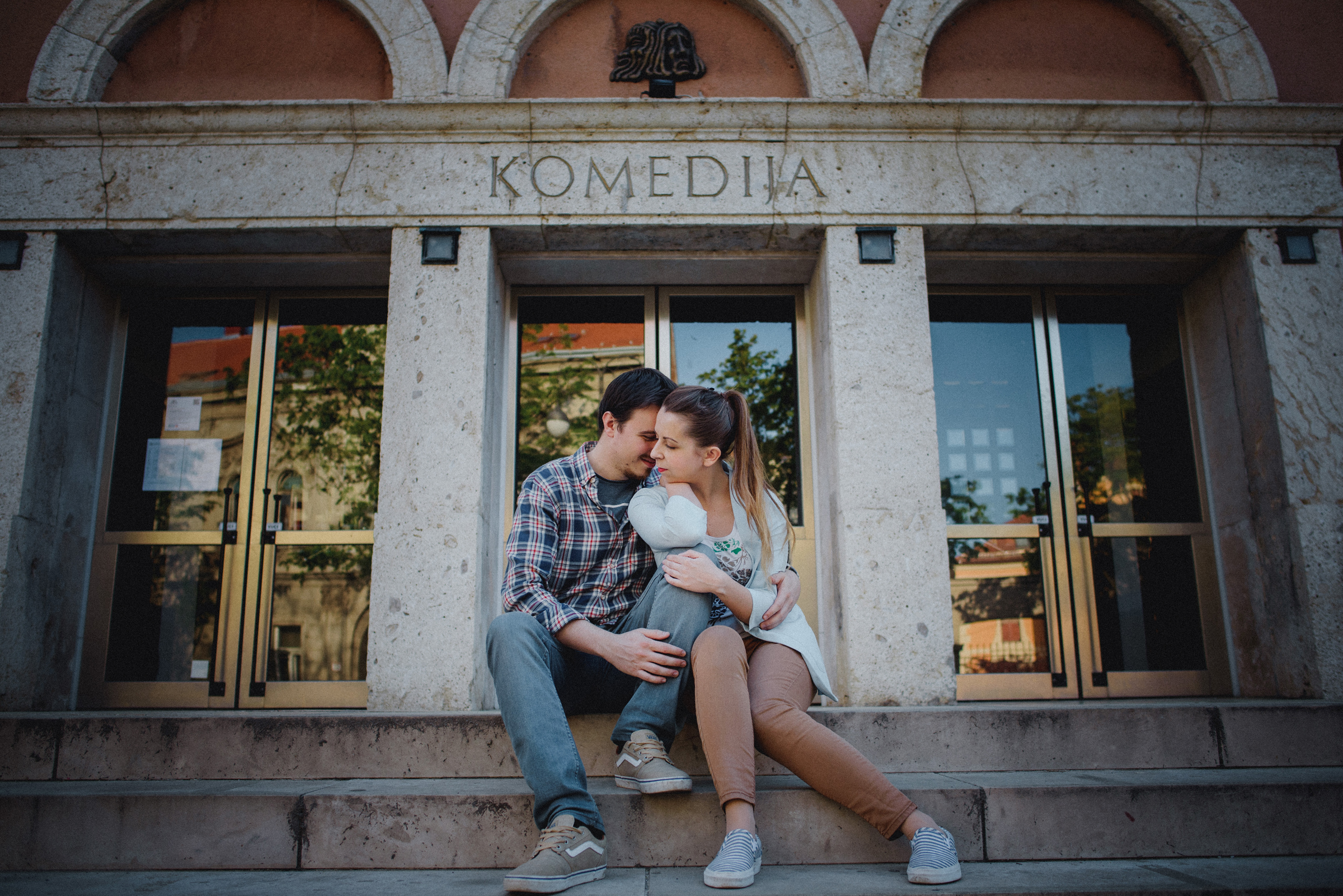 couple cuddling on stairs in front of theater Komedija in middle of Zagreb