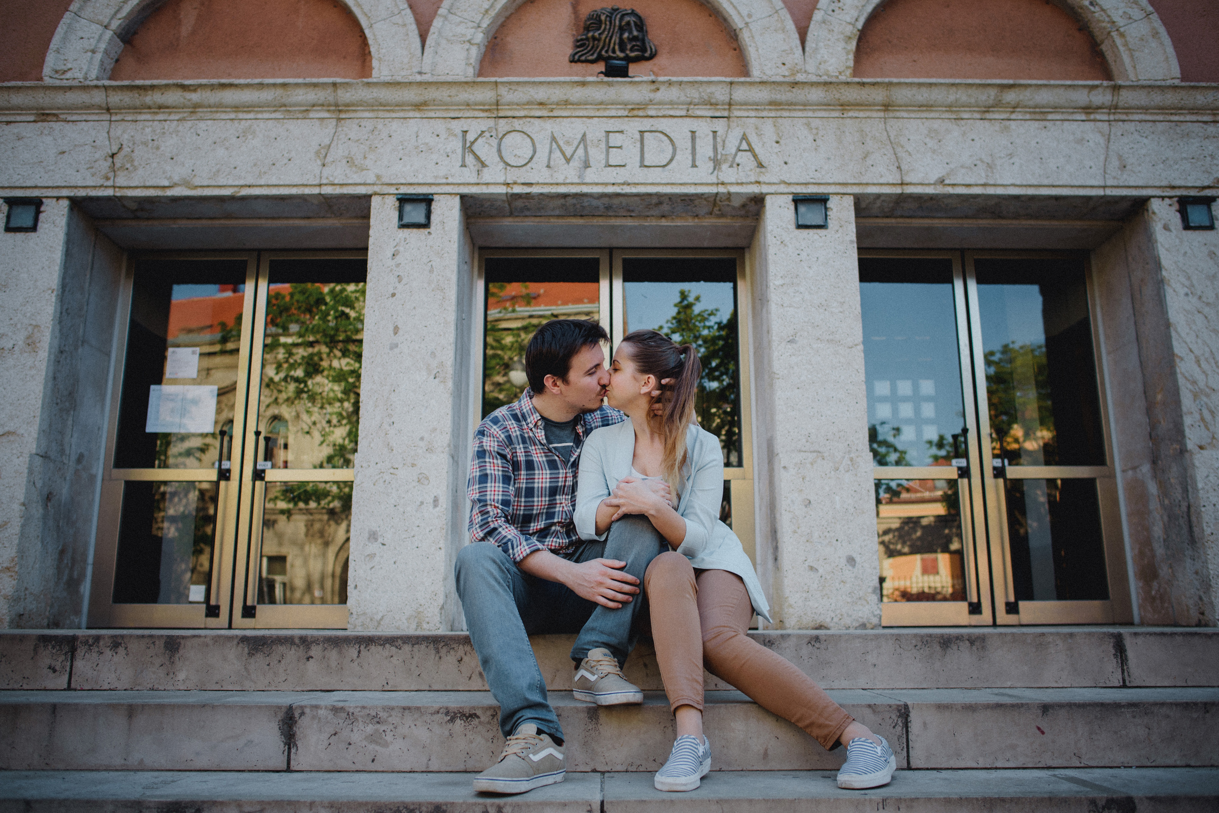 couple kissing on stairs in front of theater Komedija in middle of Zagreb