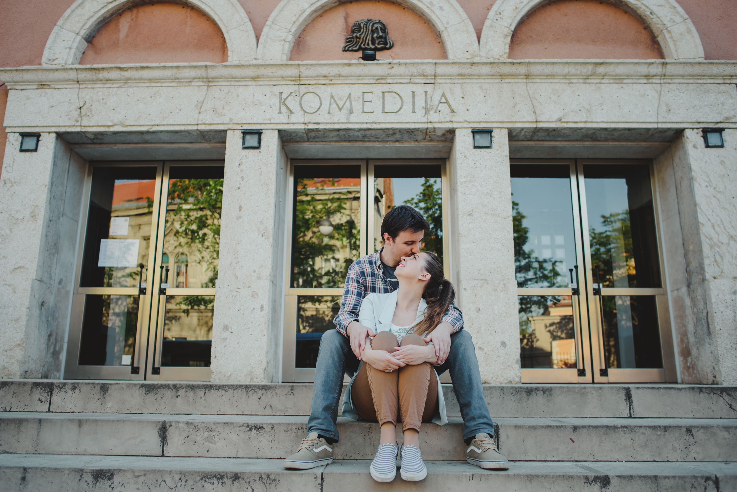 couple mingling and kissing on stairs in front of theatre Komedija in Zagreb