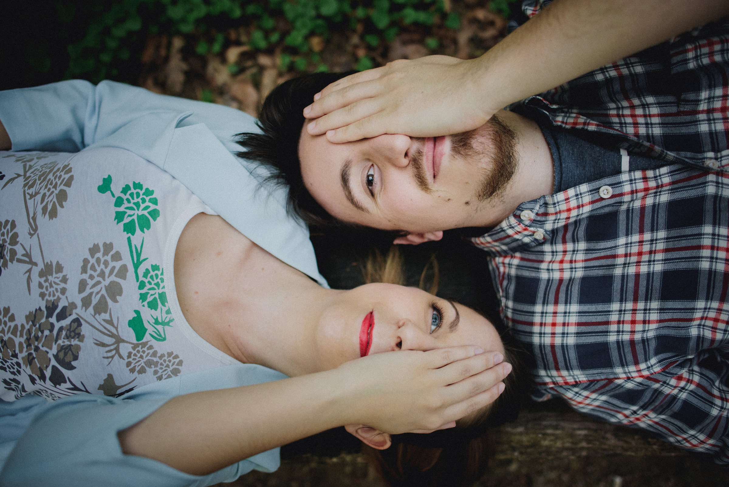 couple lying down with opposite eyes closed