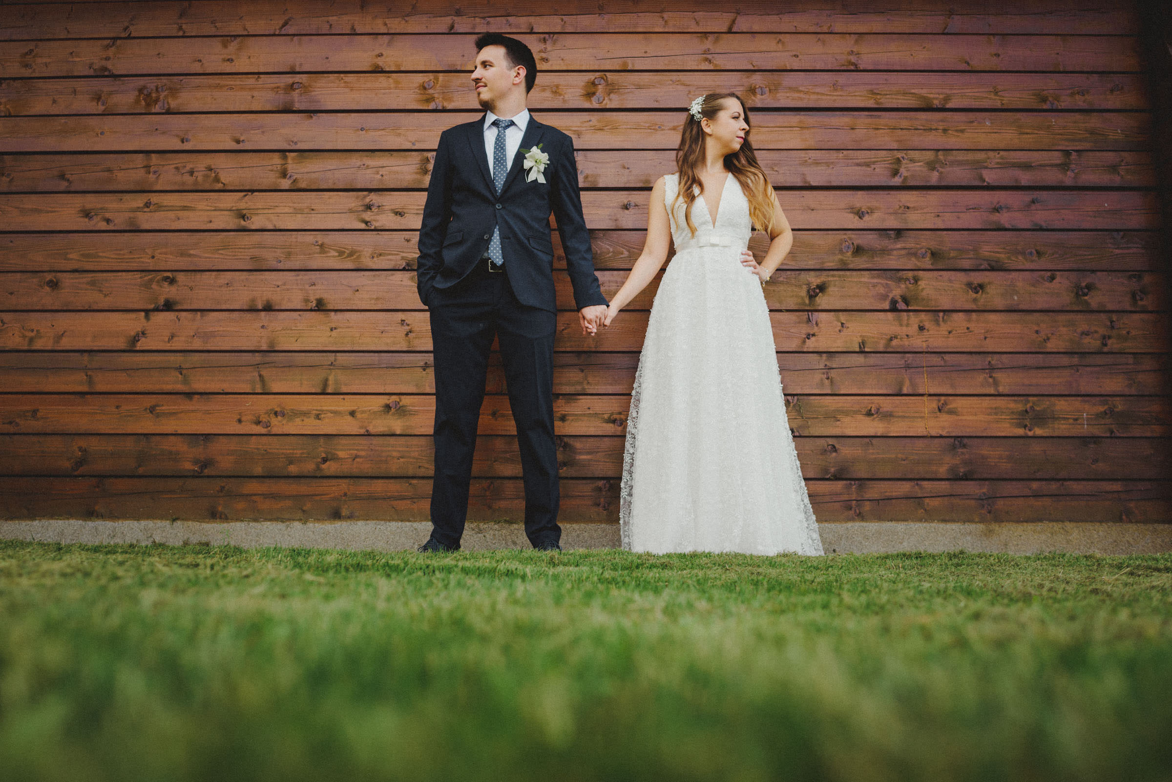 couple looking each in other way in front of wooden wall. low angle shot