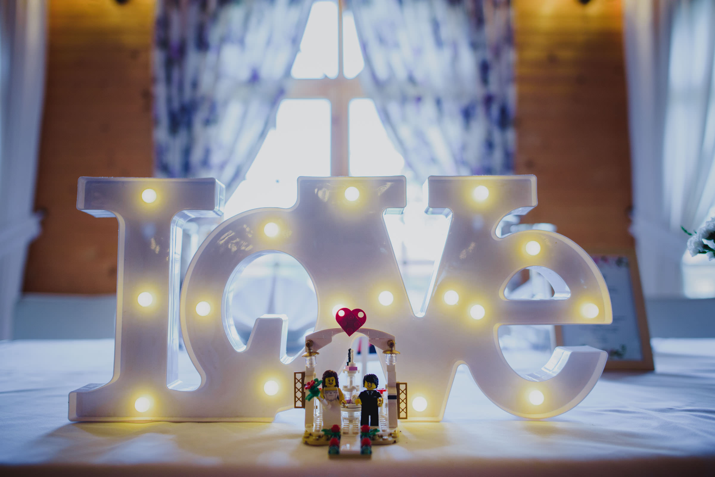 LEGO couple in front of glowing LOVE sign