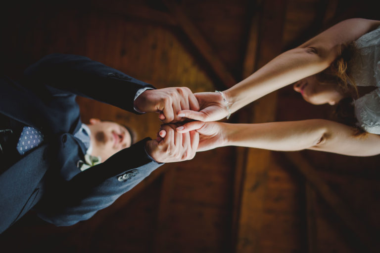 couple holding hand shot from underneath lying on a floor