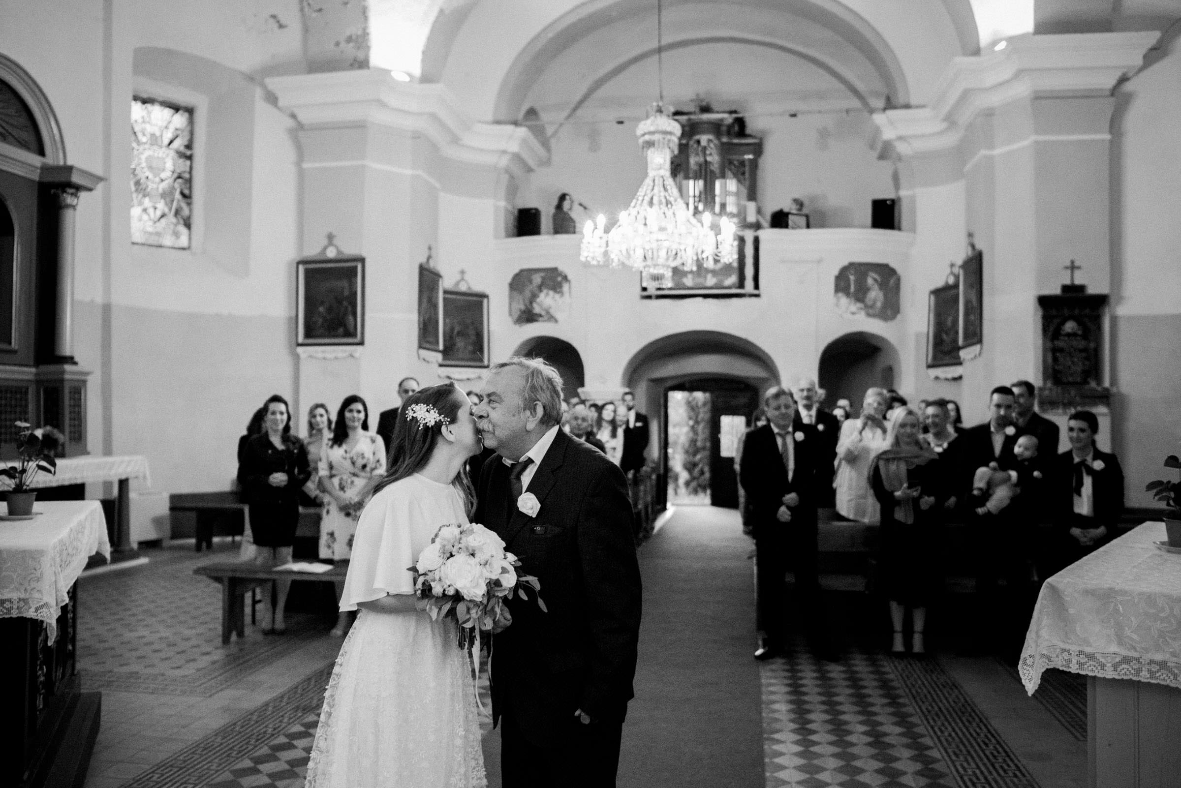 bride and her father kissing in front of the altar