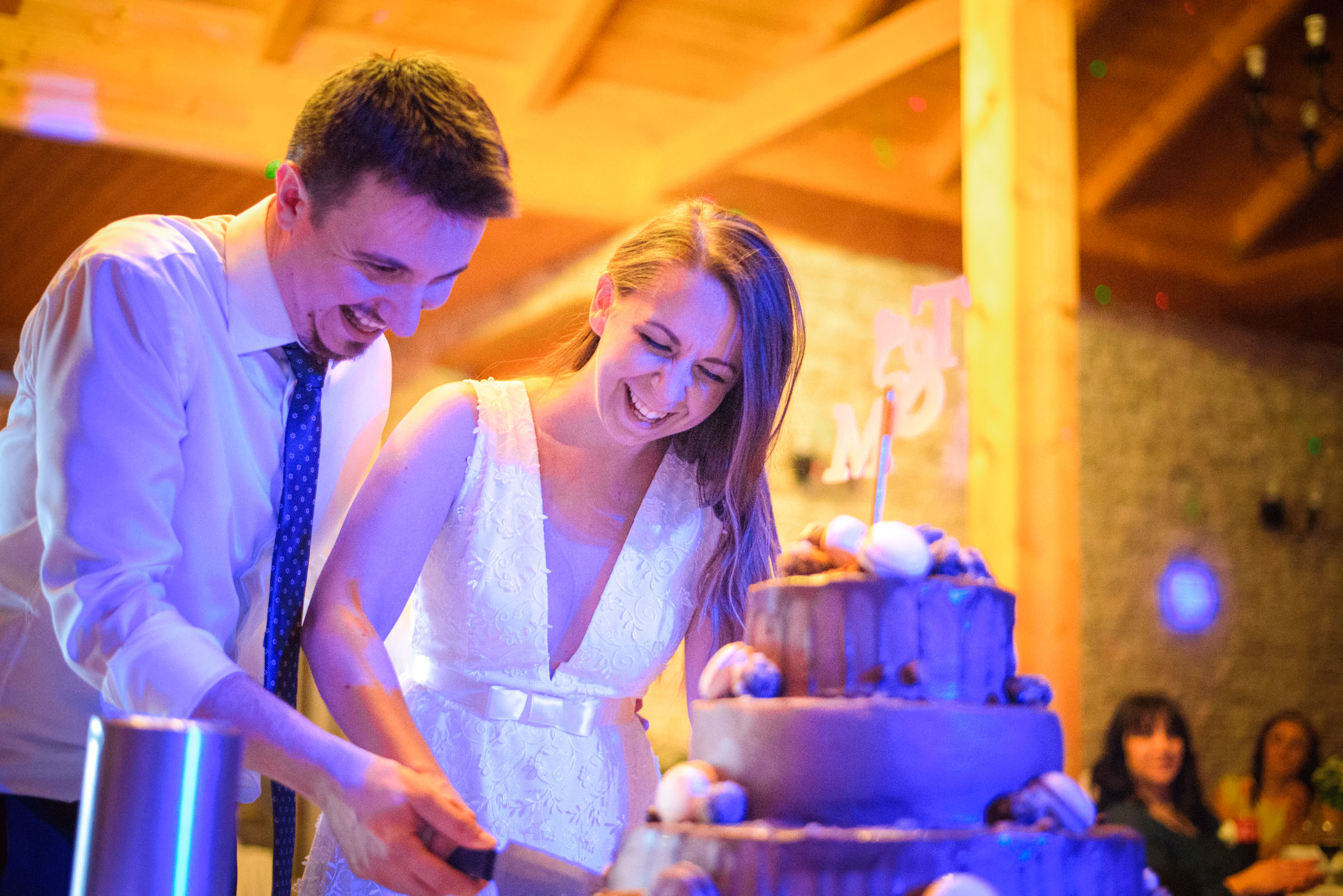 bride and groom laughing while cutting the cake