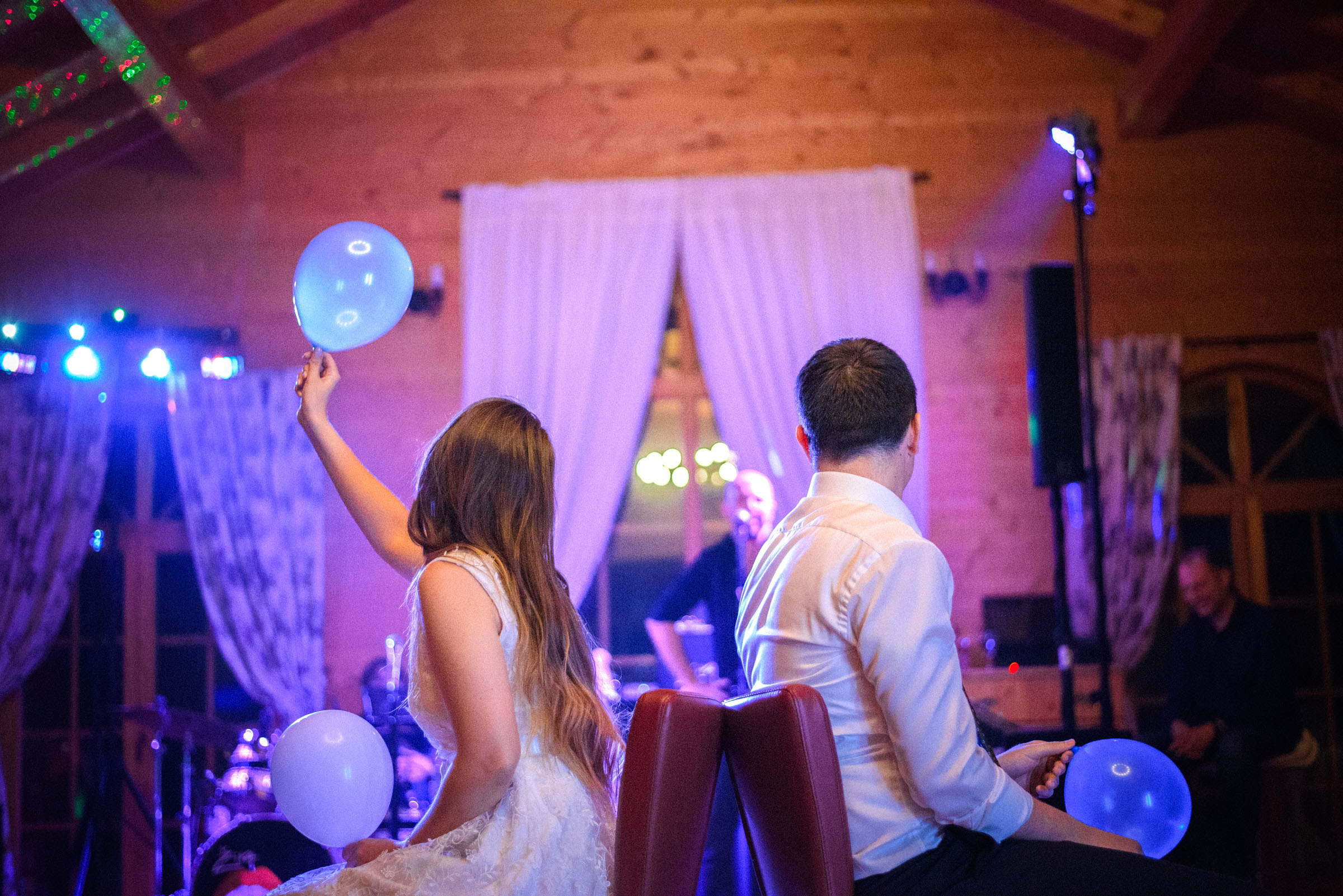 bride and groom playing game in the middle of the dance floor