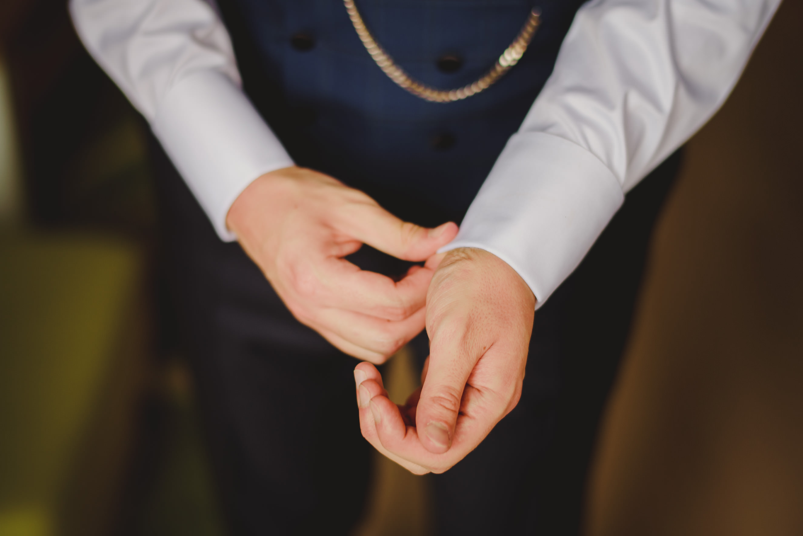 groom fixing his shirt and cufflings while getting ready for the wedding day.